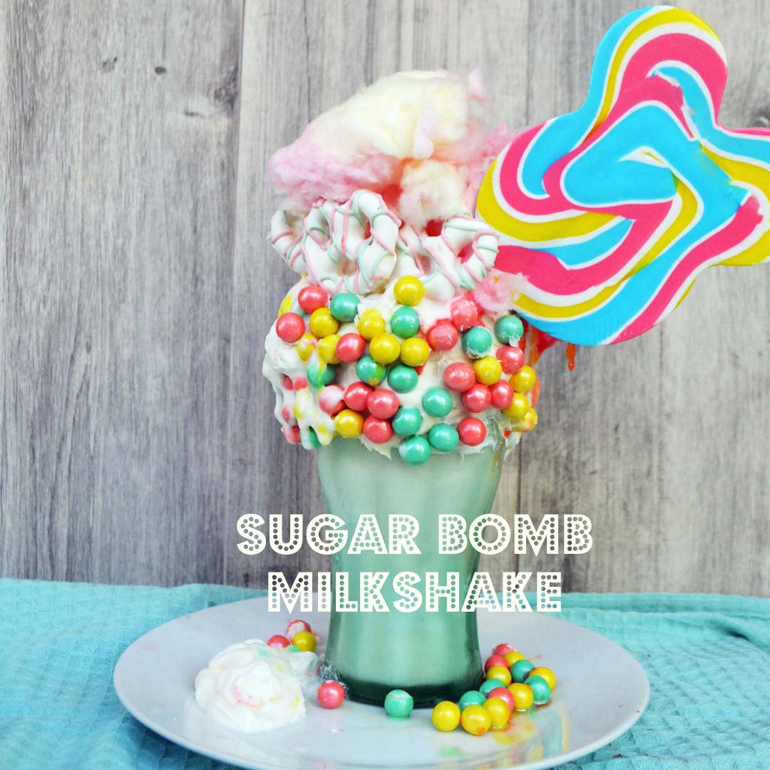 Black Tap Milkshake Copycat Recipe. The Sugar Bomb Milkshake by Modern Honey made with Vanilla Ice Cream, Sixlet Pastel Pearls, Cotton Candy, White Chocolate Covered Pretzels, Candy Sucker, and Whipped Cream. www.modernhoney.com
