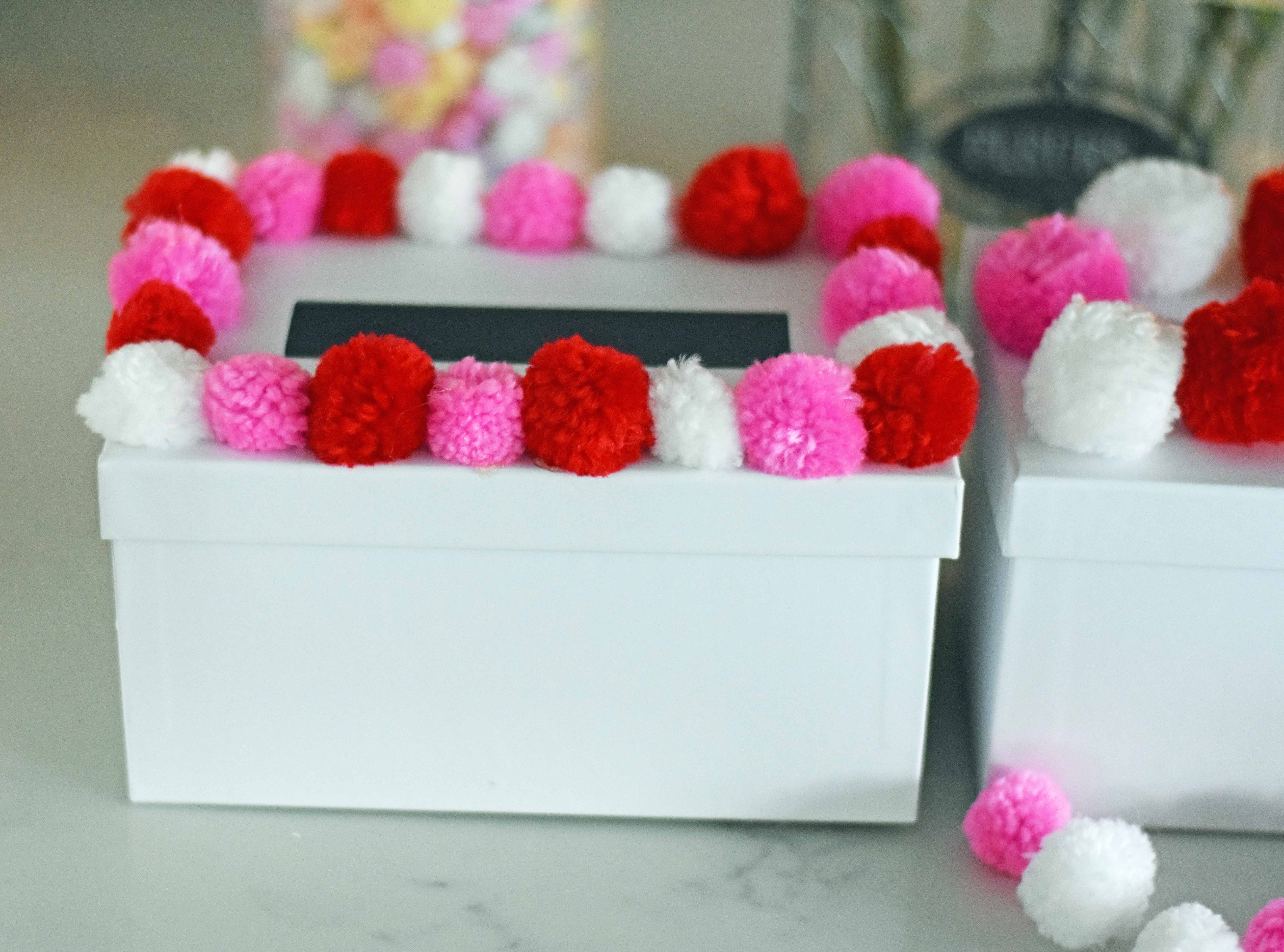 How to decorate Valentine's Day boxes with pom poms. Pom Poms Valentine's Day boxes.  Easy Valentine's Day boxes for school. Valentine's Day decorating ideas. www.modernhoney.com