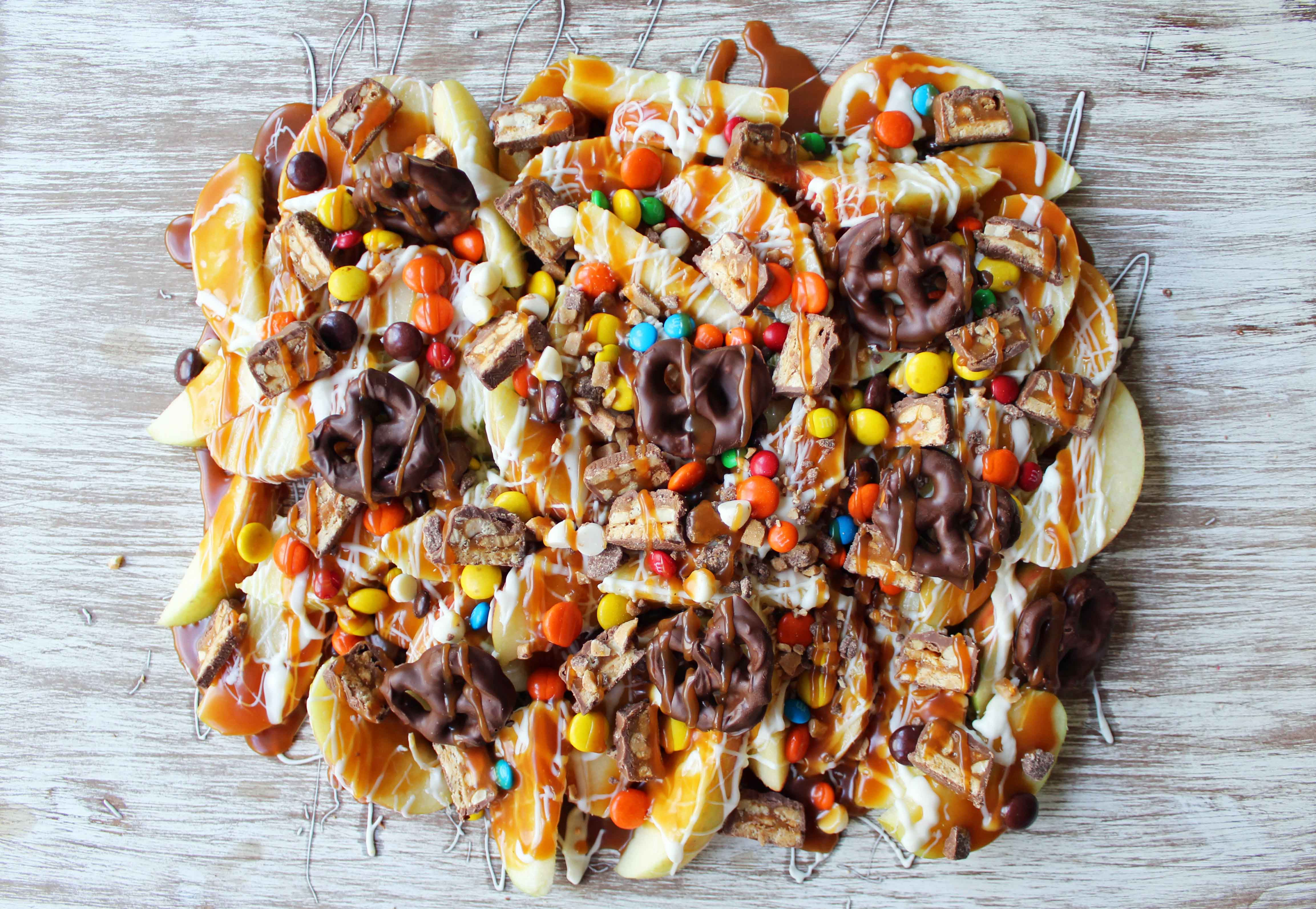 Candy Madness Caramel Apple Nachos by Modern Honey. Crisp Apples topped with Salted Caramel, White Chocolate, M &M's, Reeses Pieces, Heath Toffee Bits, Snickers, and Chocolate Covered Pretzels. These Caramel Apple Nachos are much easier than making caramel apples and will be a huge hit at your next party!