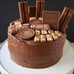 Candy Bar Stash Chocolate Cake. A 5 star rated moist chocolate cake recipe with perfect chocolate buttercream topped with chocolate candy bars. The perfect birthday cake for the chocolate lover or Halloween cake. www.modernhoney.com