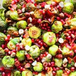 Bacon Roasted Brussell Sprouts with Pomegranates by Modern Honey. Roasted Brussell Sprouts in Extra Virgin Olive Oil, Crispy Bacon, Pomegranates, and Hazelnuts. The perfect healthy Thanksgiving side dish.