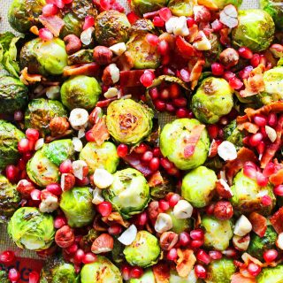 Bacon Roasted Brussels Sprouts with Pomegranates by Modern Honey. Roasted Brussels Sprouts in Extra Virgin Olive Oil, Crispy Bacon, Pomegranates, and Hazelnuts. The perfect healthy Thanksgiving side dish.