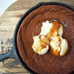 Gingerbread Skillet Cookie with Caramel Sauce by Modern Honey. Perfectly spiced and soft gingerbread cookie topped with vanilla ice cream and caramel sauce.