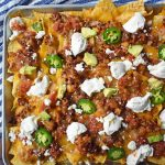 Ultimate Spicy Beef Nachos by Modern Honey. Layers of spicy beef, refried beans, mexican cheese, sour cream, avocado, and jalapenos. These are the perfect party snack for your next party!