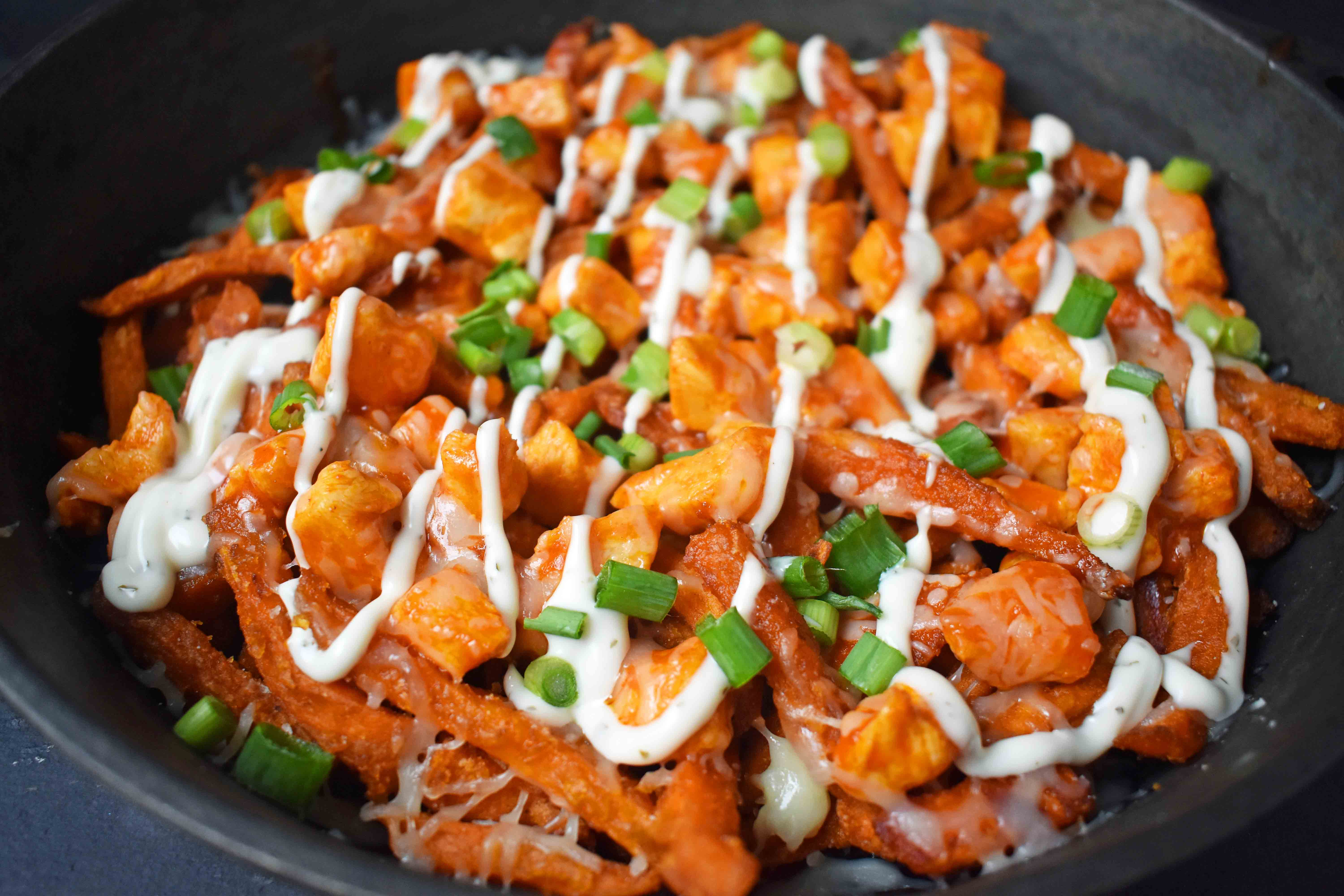 Buffalo Chicken Sweet Potato Fries by Modern Honey. Crisp Sweet Potato Fries topped with Buffalo Wing Chicken, Cheese, Green Onions, and Ranch Dressing.