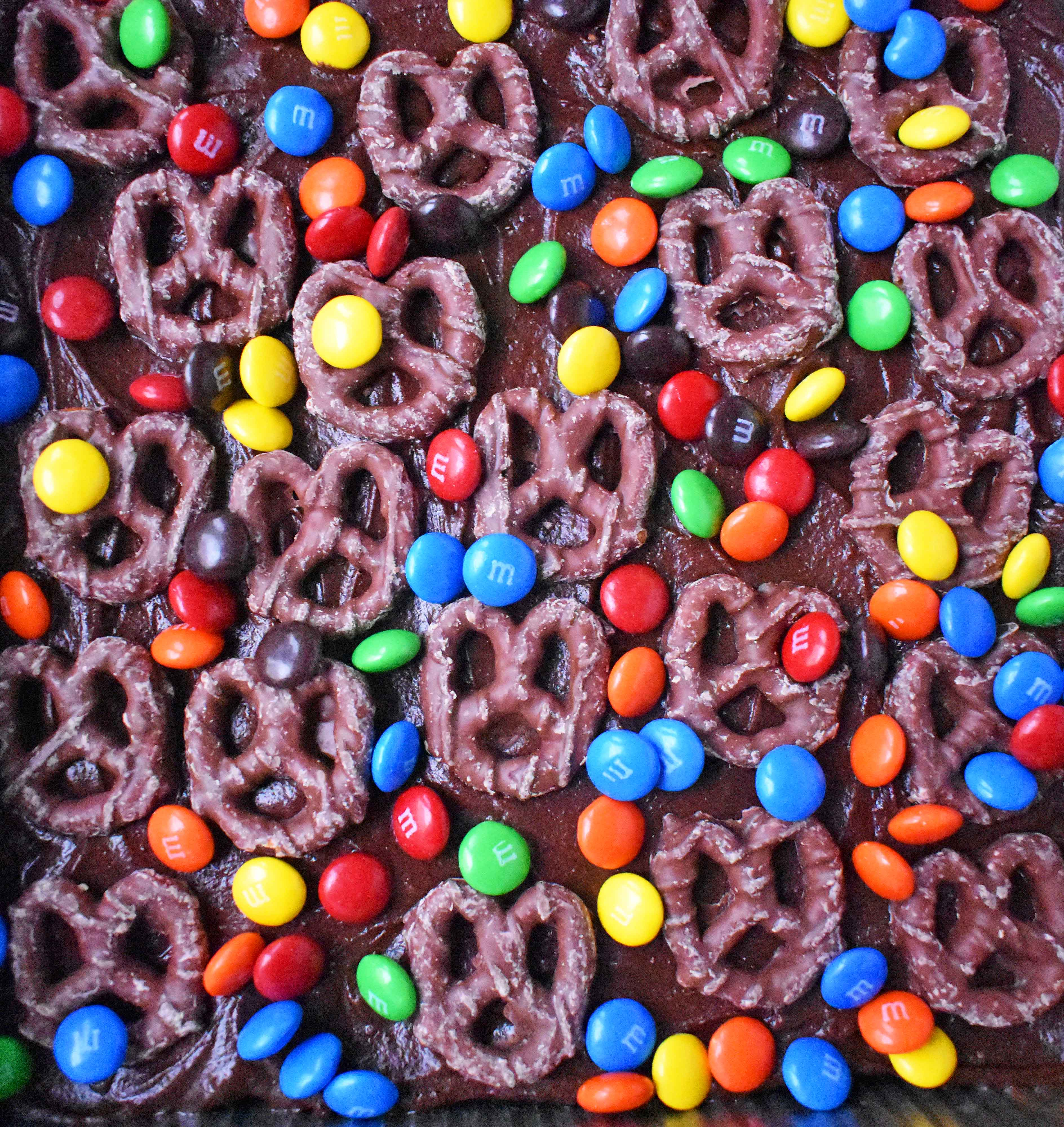 Super Bowl Chocolate Covered Pretzel Brownies. Chewy rich chocolate chunk brownies topped with creamy frosting, chocolate covered pretzels, and M & M's. www.modernhoney.com