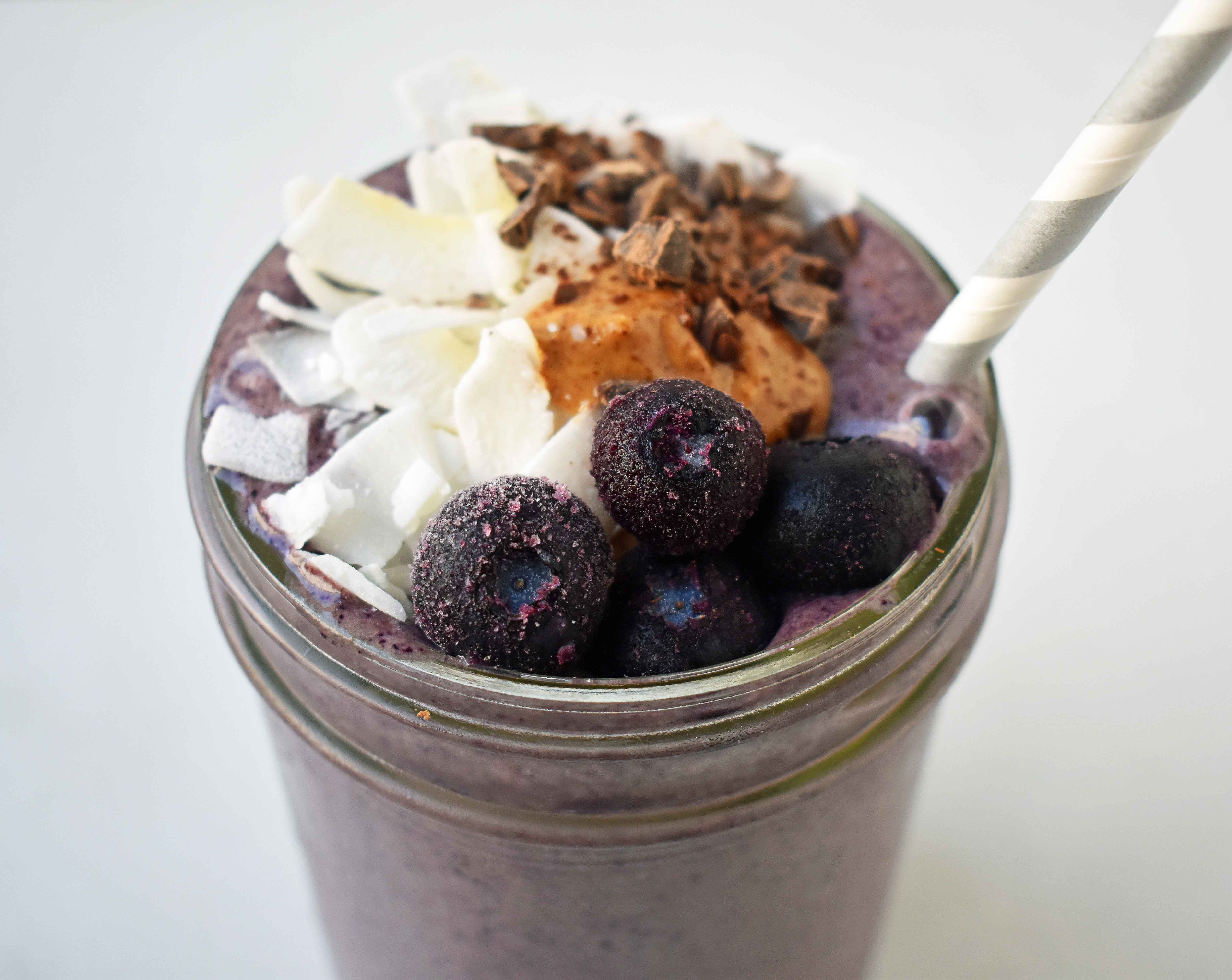 Wild Blueberry Chocolate Coconut Smoothie. Made with chocolate protein powder, coconut milk, blueberries, almond butter, banana, cacao powder. Topped with blueberries, almond butter, and dark chocolate shavings. A craveworthy chocolate coconut protein shake packed with nutrition. www.modernhoney.com