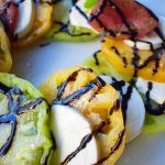 Heirloom Tomato Caprese Salad by Modern Honey. Garden Heirloom tomatoes layered with fresh mozzarella slices, extra virgin olive oil, balsamic glaze, salt, and fresh basil. A beautiful and healthy appetizer. www.modernhoney.com
