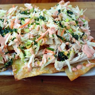 Asian Wonton Chicken Nachos. Fried wontons, pulled chicken, sriracha cream, cabbage mix, and sweet cilantro sauce. An Asian twist on nachos for the perfect party appetizer.