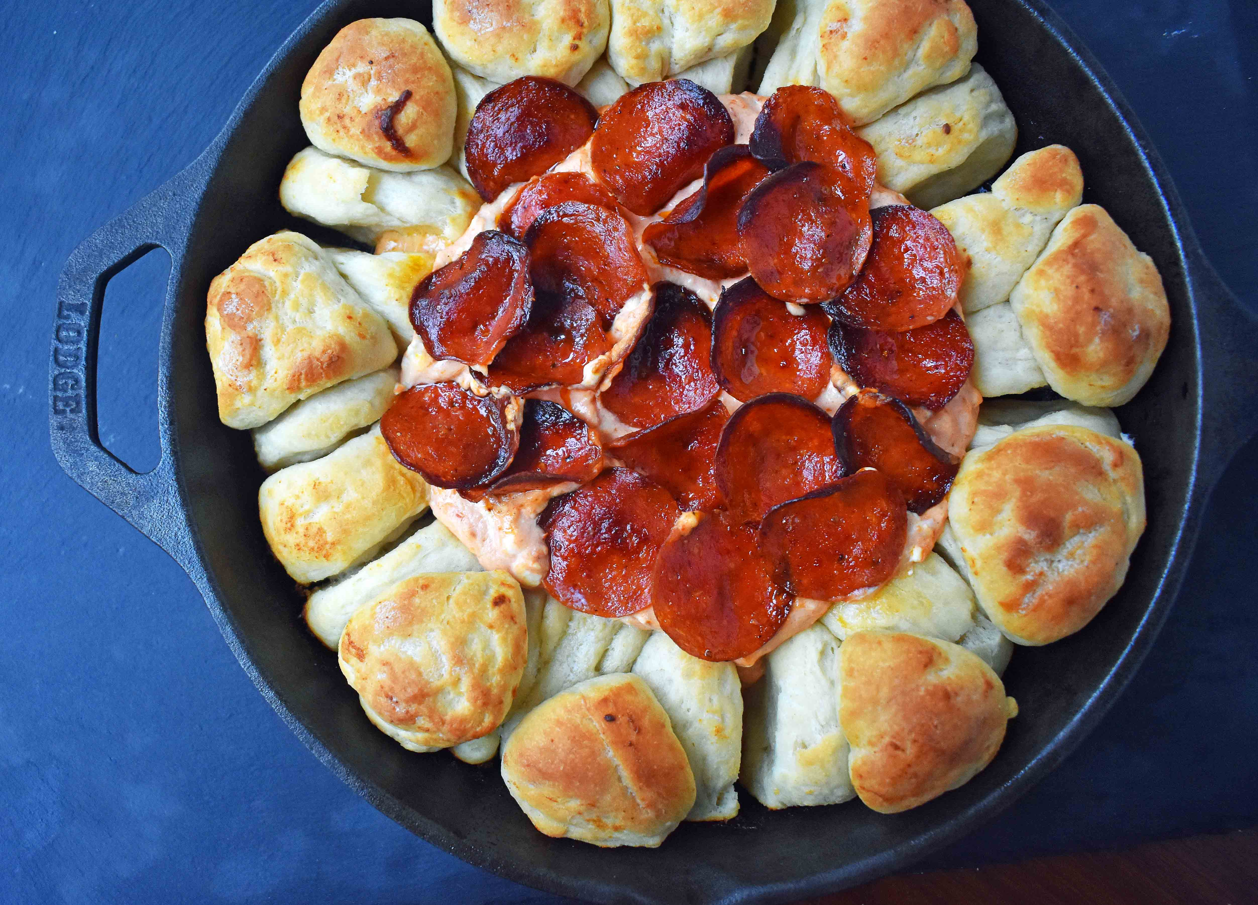Pepperoni Pizza Dip with Pizza Crust Dippers by Modern Honey. Creamy pizza dip topped with crispy pepperoni and baked with garlic butter pizza rolls. All baked in a cast iron skillet. www.modernhoney.com