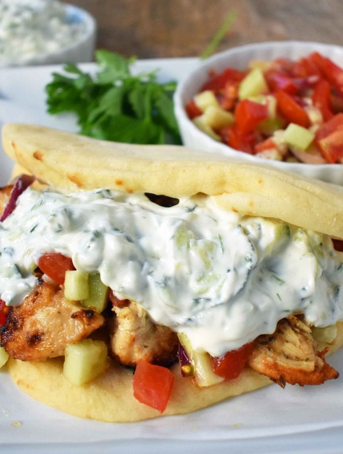 Greek Chicken Gyros with Tzatziki Sauce. Marinated Greek Chicken, grilled to perfection and topped with homemade tzatziki sauce and fresh Greek salad. A healthy and flavorful dish. www.modernhoney.com