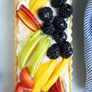 Fresh Fruit Tart with Vanilla Pastry Cream. Buttery, flaky tart filled with homemade vanilla bean custard and topped with fresh fruits. A classic French dessert that is a huge crowd pleaser. www.modernhoney.com