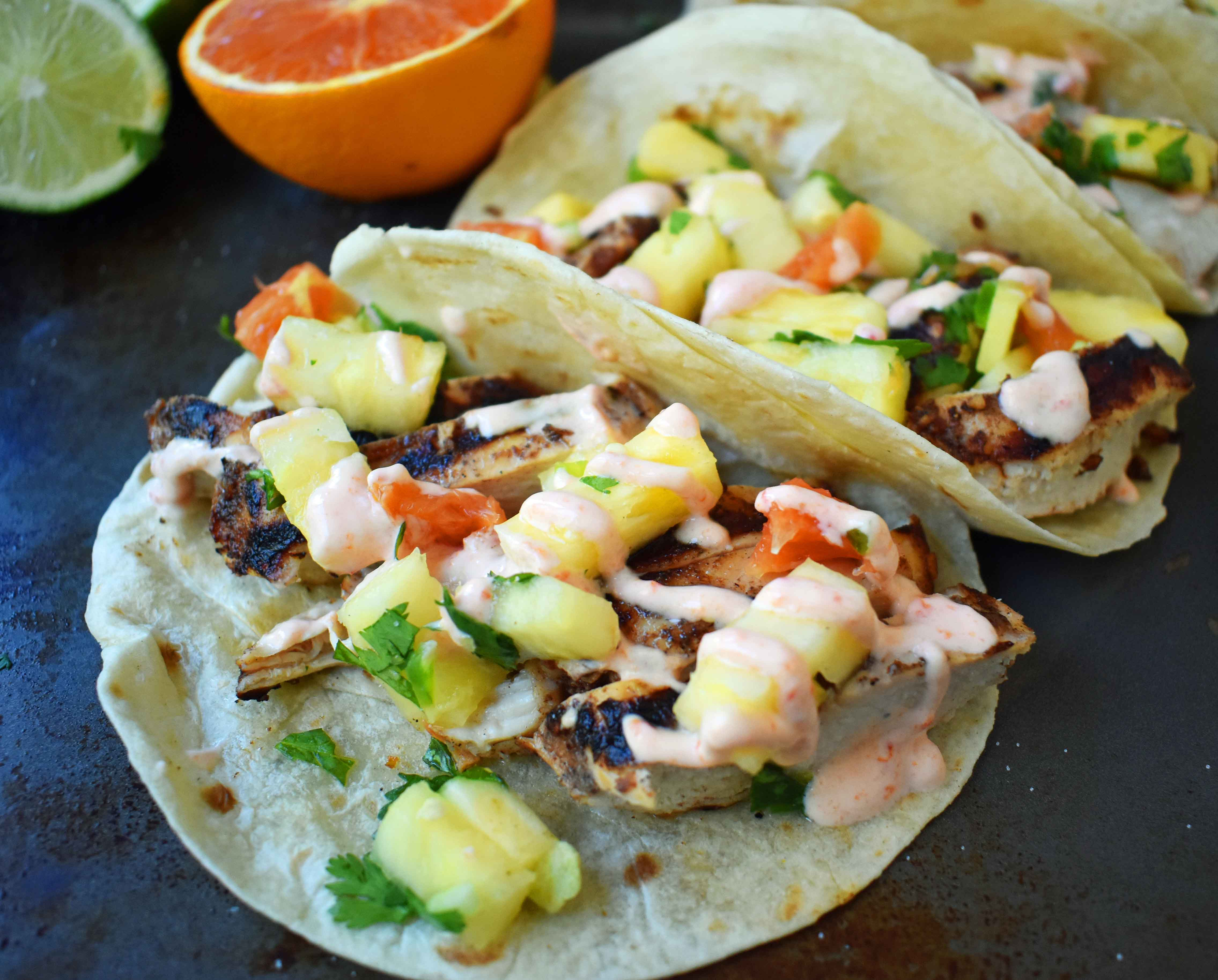 Jamaican Jerk Chicken Tacos. Caribbean spiced citrus grilled chicken filled tacos with pineapple salsa and spicy cream. www.modernhoney.com