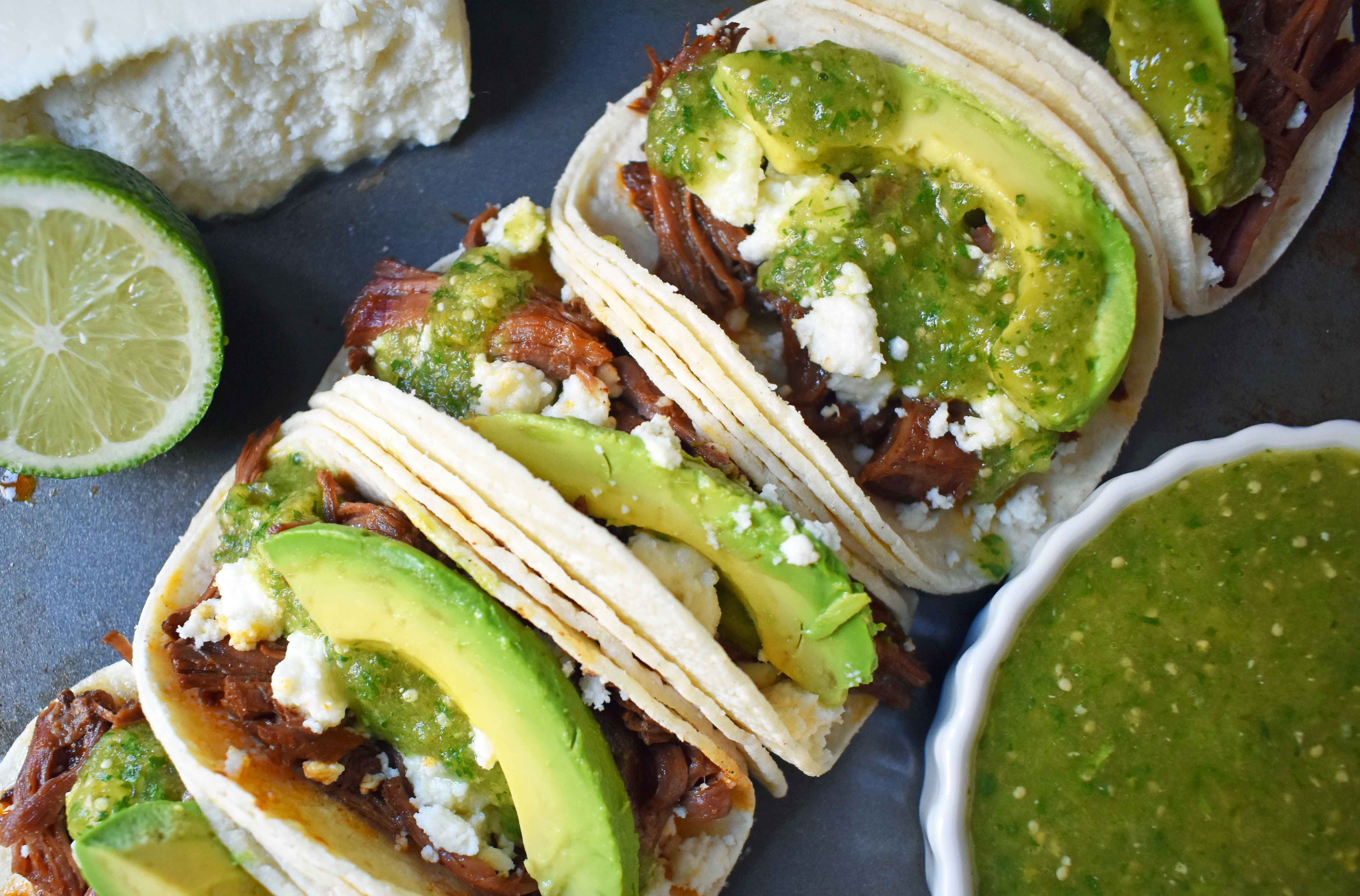 Slow Cooker Beef Barbacoa Tacos with Homemade Tomatillo Salsa. Tender spicy beef barbacoa made in slow cooker and topped with fresh avocado, queso fresco cheese, and homemade tomatillo salsa. www.modernhoney.com