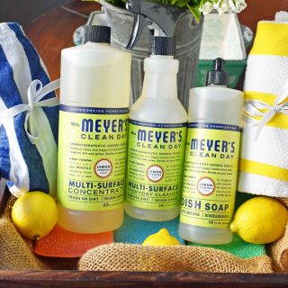 The Perfect Housewarming Basket. A basket full of Mrs. Meyer's Lemon Verbena Multi-Surface Everyday Cleaner, Mrs. Meyer's Dish Soap, striped dish towels, colorful sponges, fresh lemons and a vibrant tablecloth. www.modernhoney.com