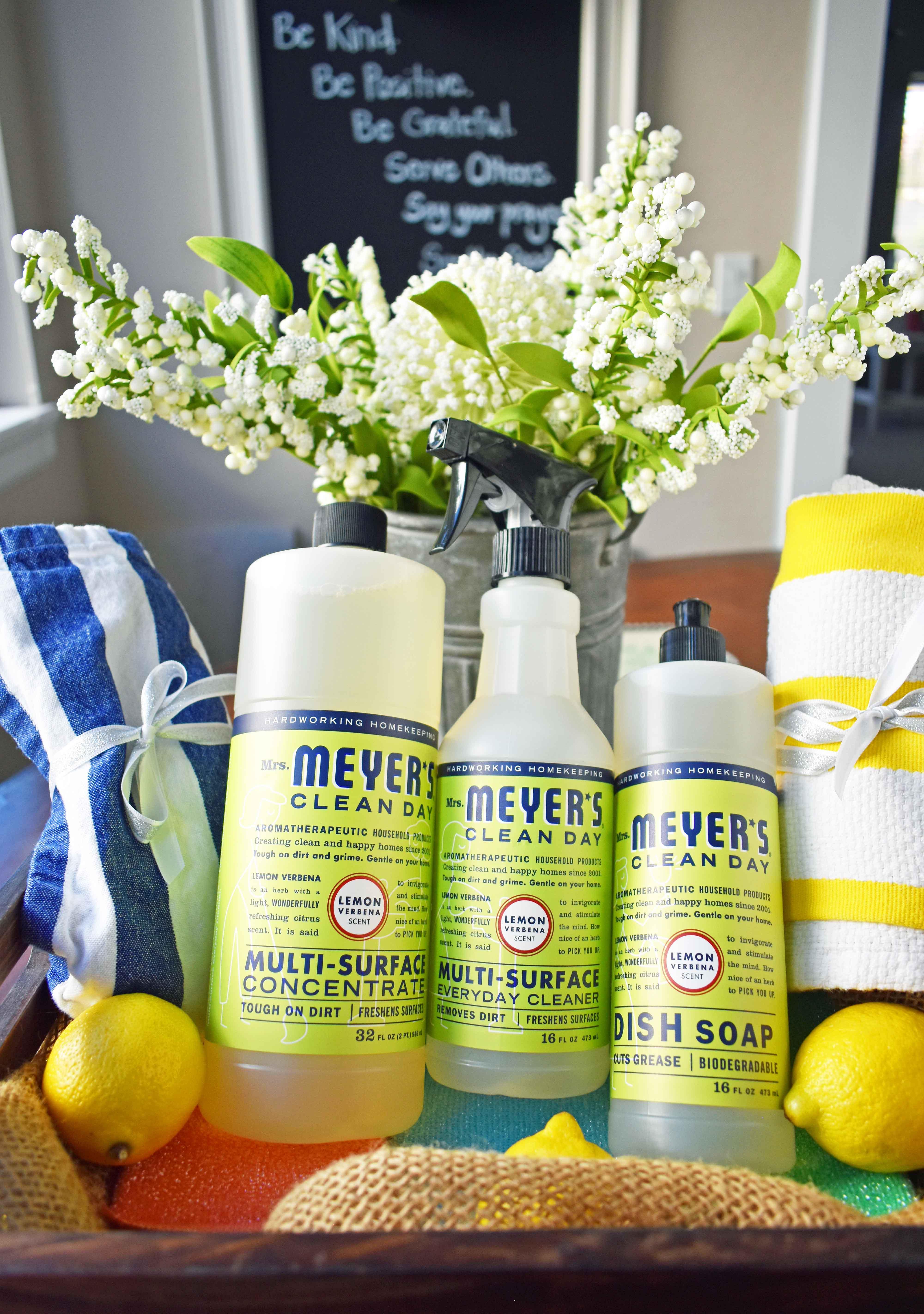 The Perfect Housewarming Basket. A basket full of Mrs. Meyer's Lemon Verbena Multi-Surface Everyday Cleaner, Mrs. Meyer's Dish Soap, striped dish towels, colorful sponges, fresh lemons and a vibrant tablecloth. www.modernhoney.com