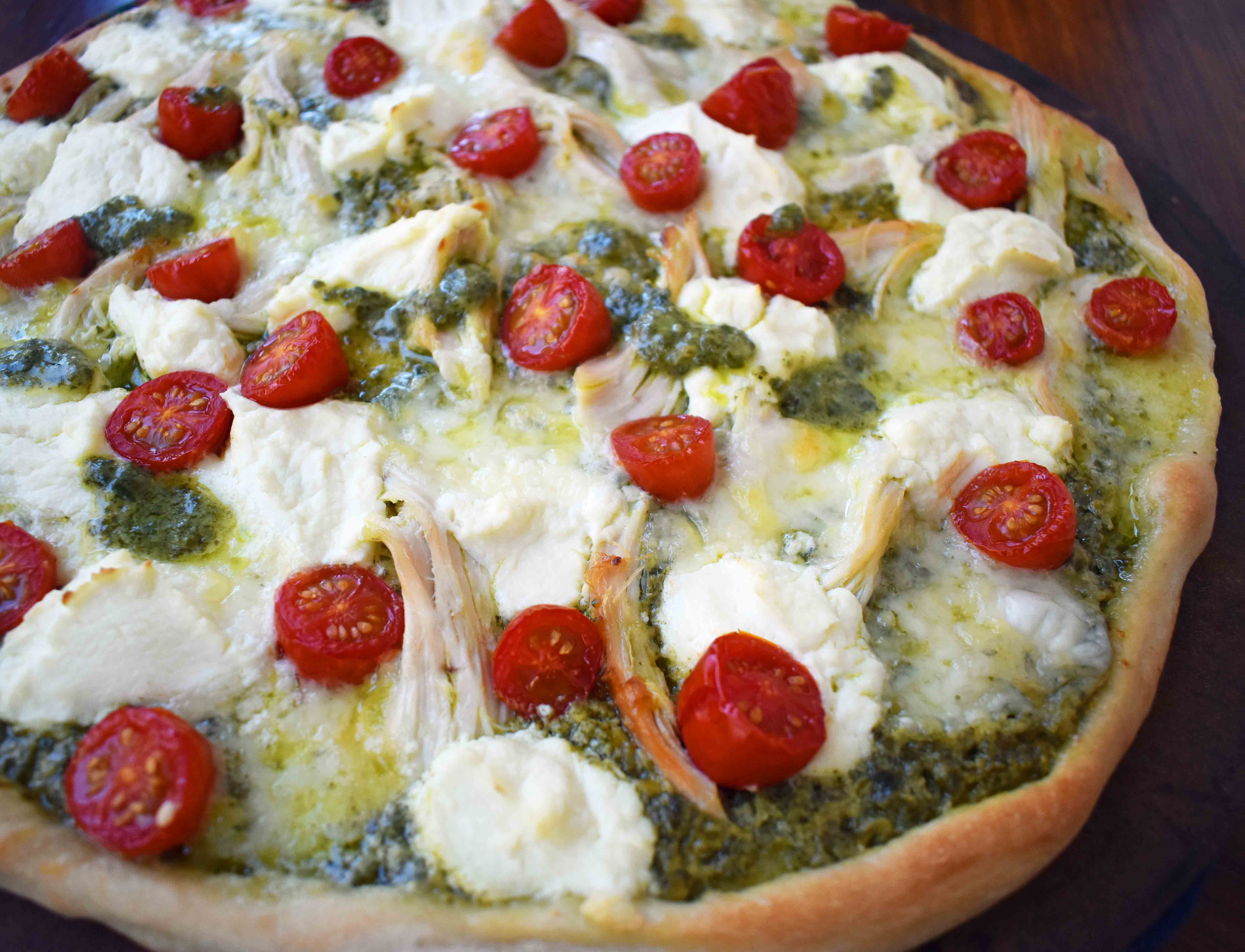 Chicken Pesto Pizza made with only 5 ingredients -- refrigerated pizza dough, pesto sauce, rotisserie chicken, ricotta cheese, and fresh mozzarella. May add grape tomatoes if so desired. An easy, flavorful homemade white pizza. www.modernhoney.com
