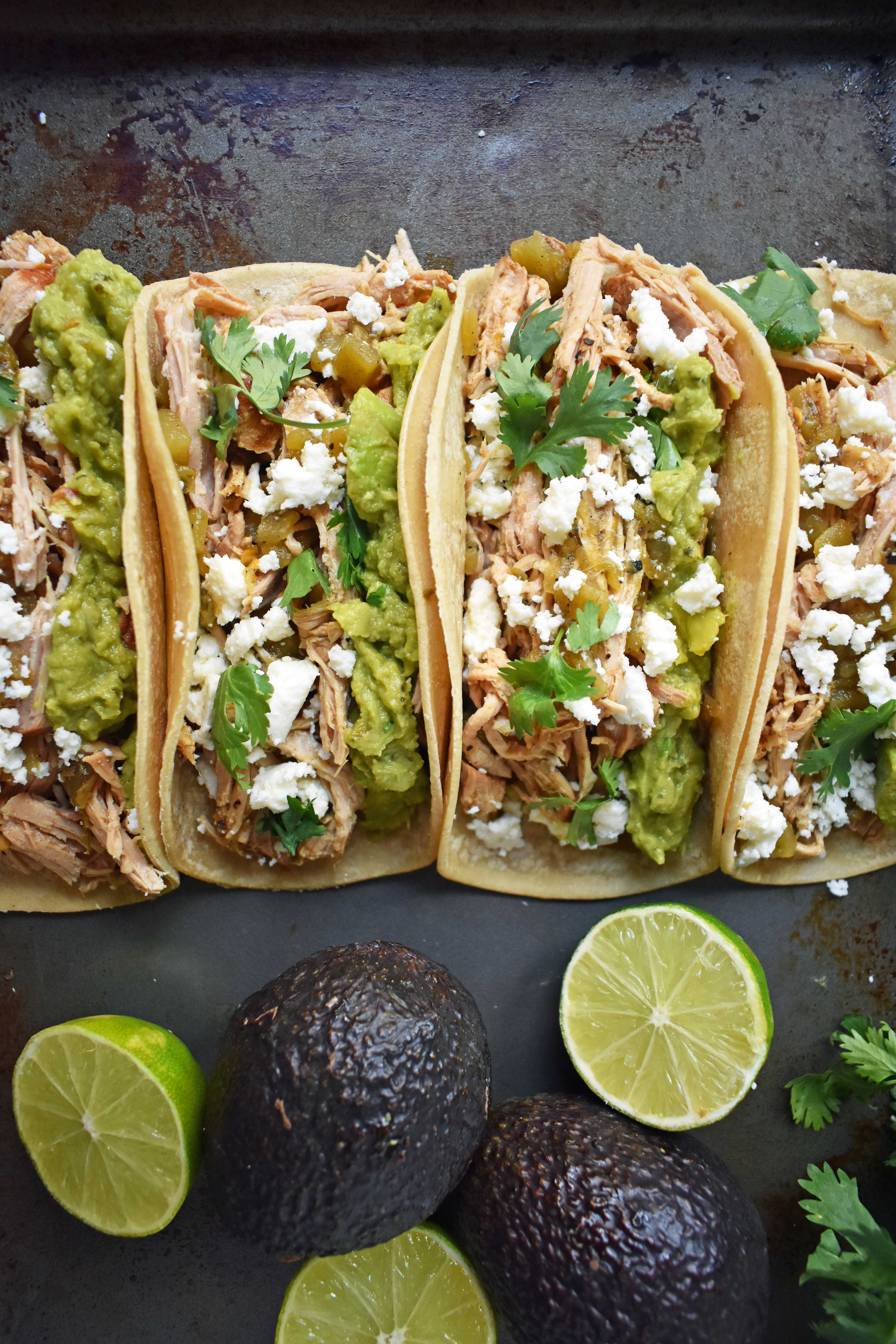 Green Chili Pork Carnitas Tacos. Slow cooked green chili pork seasoned with Mexican spices and freshly squeezed lime juice placed in a hot corn tortilla and topped with cotija cheese, jalapenos, avocado and cilantro. www.modernhoney.com