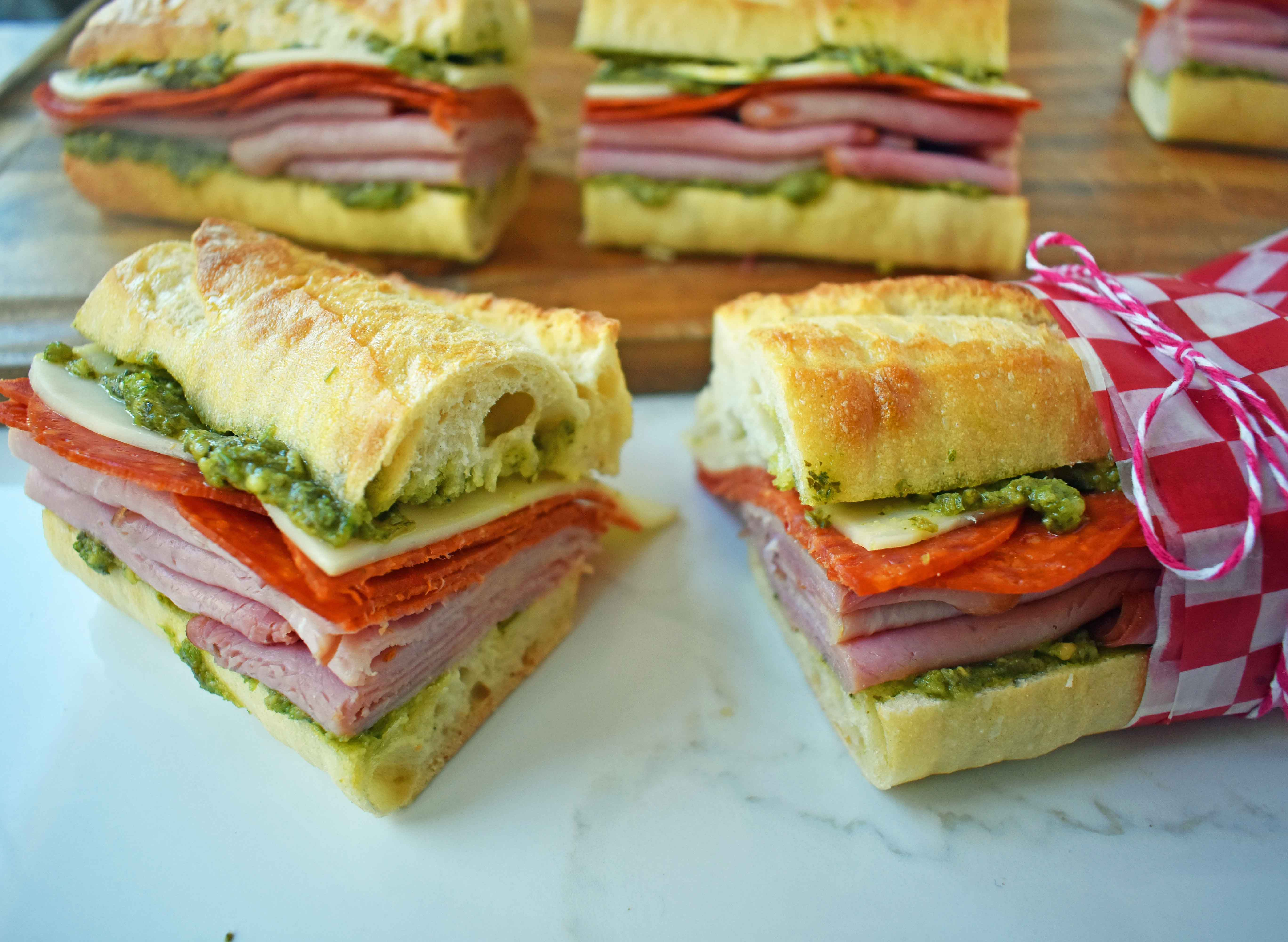 Italian Pressed Sandwiches made with rustic French bread layered with Italian meats and cheeses, pesto sauce or olive oil and vinegar, and marinated tomatoes. This Italian Pressed Sandwich with pesto sauce is perfect for a picnic, kids lunch, or for a casual lunch. www.modernhoney.com