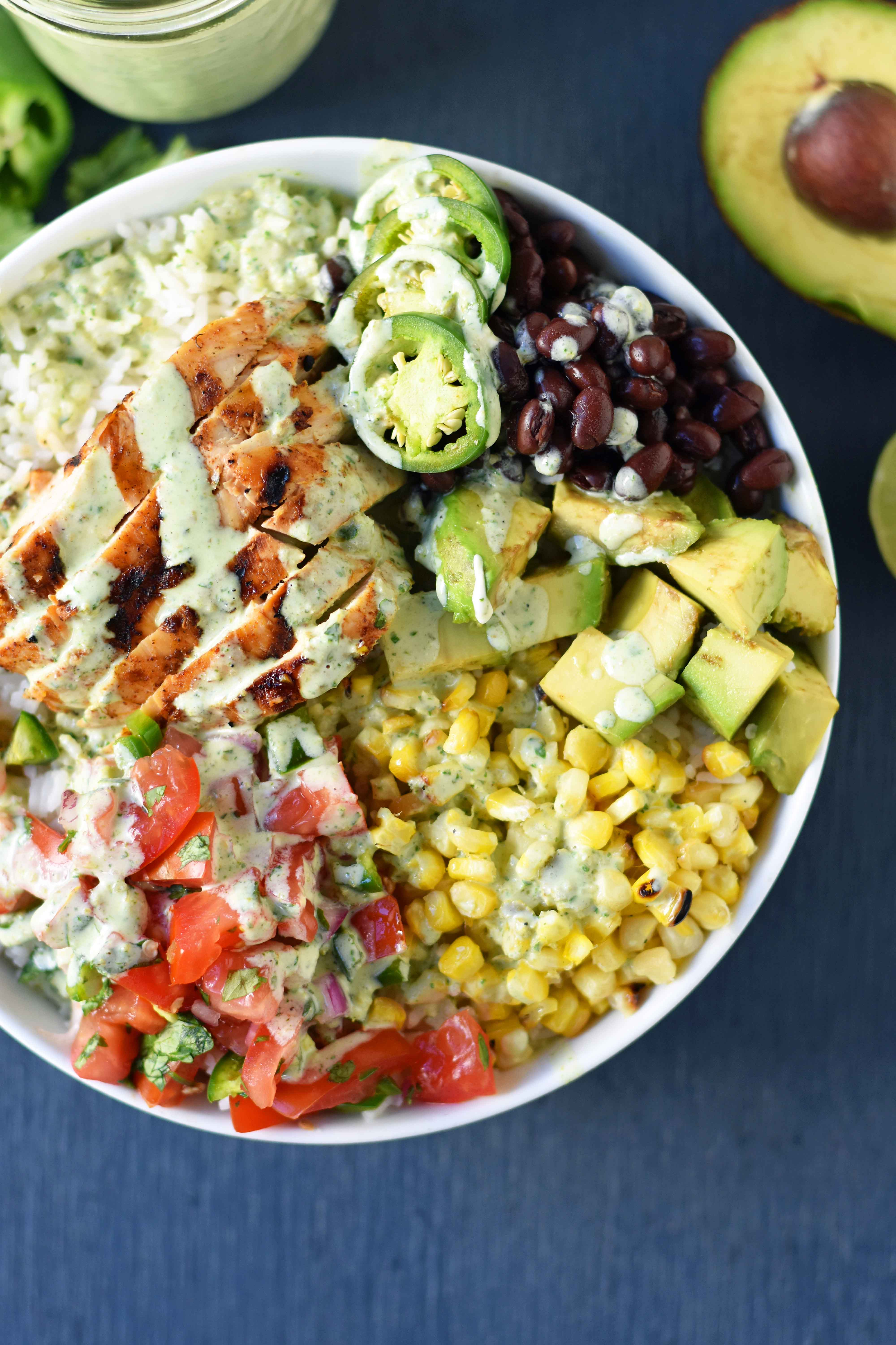 Grilled Chicken Burrito Bowls. Chipotle burrito bowls copycat recipe. Chili lime grilled chicken, pico de gallo, avocado, roasted corn, black beans, rice, and cilantro ranch dressing. A healthy mexican chicken taco bowl. www.modernhoney.com