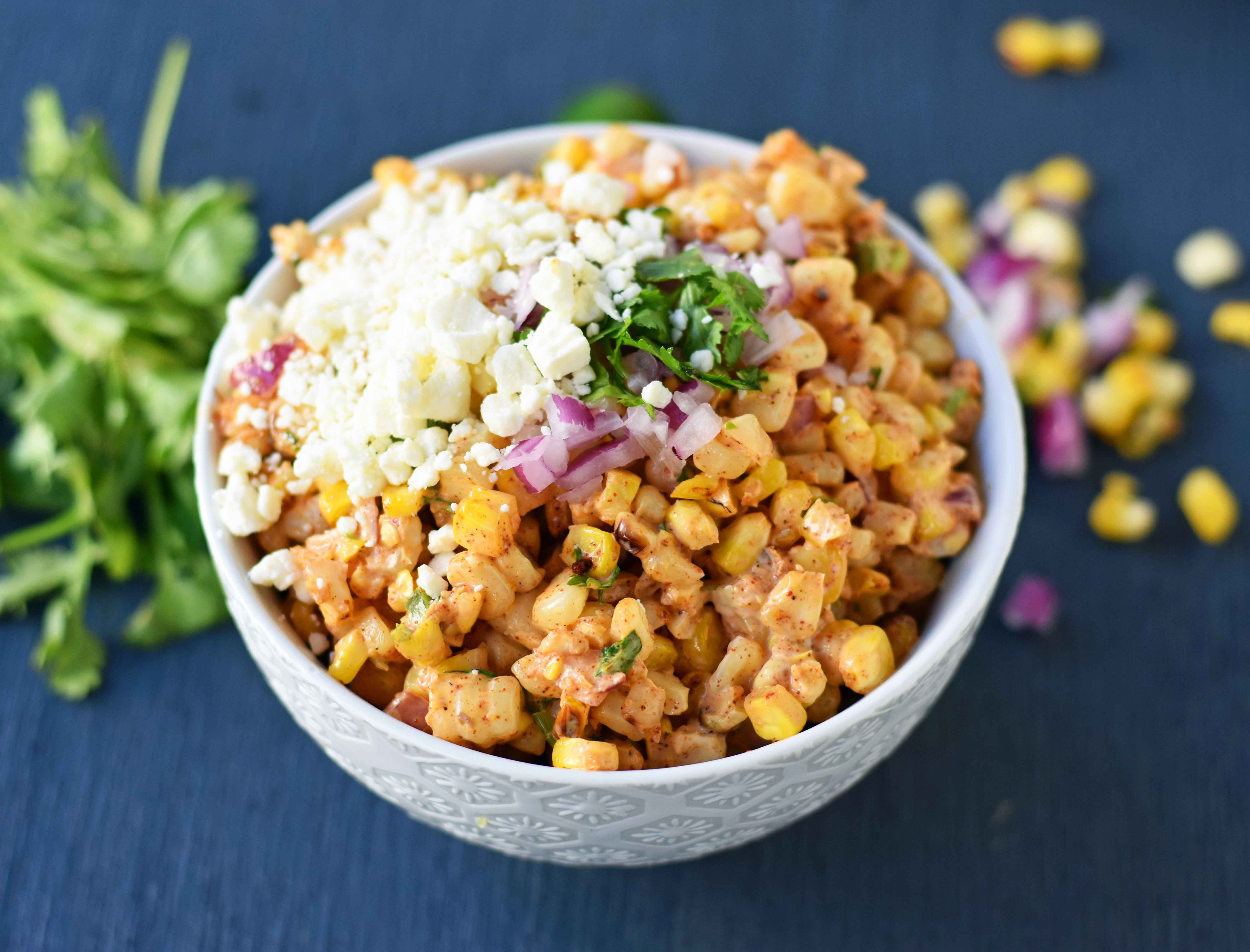 Mexican Street Corn Salad. Mexican Street Corn in a bowl made with roasted corn, mexican spices, lime, cilantro, a touch of mayo, and cotija cheese. A perfect mexican side dish or mexican appetizer. This street corn is great on tacos too! www.modernhoney.com