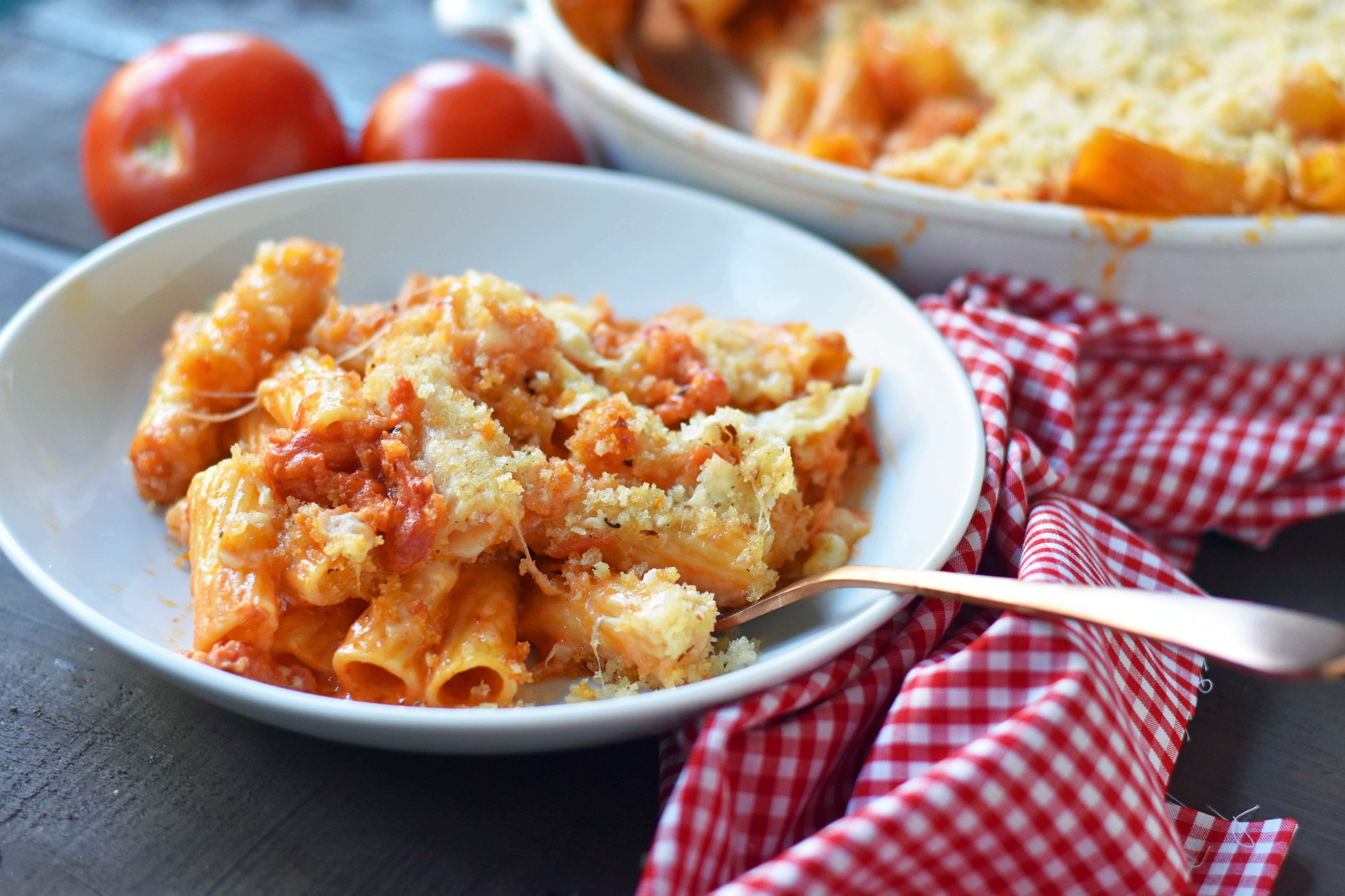 Cheesy Baked Rigatoni. An easy, popular Italian pasta dish. Baked rigatoni or baked ziti with rich and creamy bechamel sauce and homemade marinara sauce topped with parmesan and mozzarella cheeses and with olive oil crunchy topping. A family favorite weeknight pasta dish made in 30 minutes. www.modernhoney.com