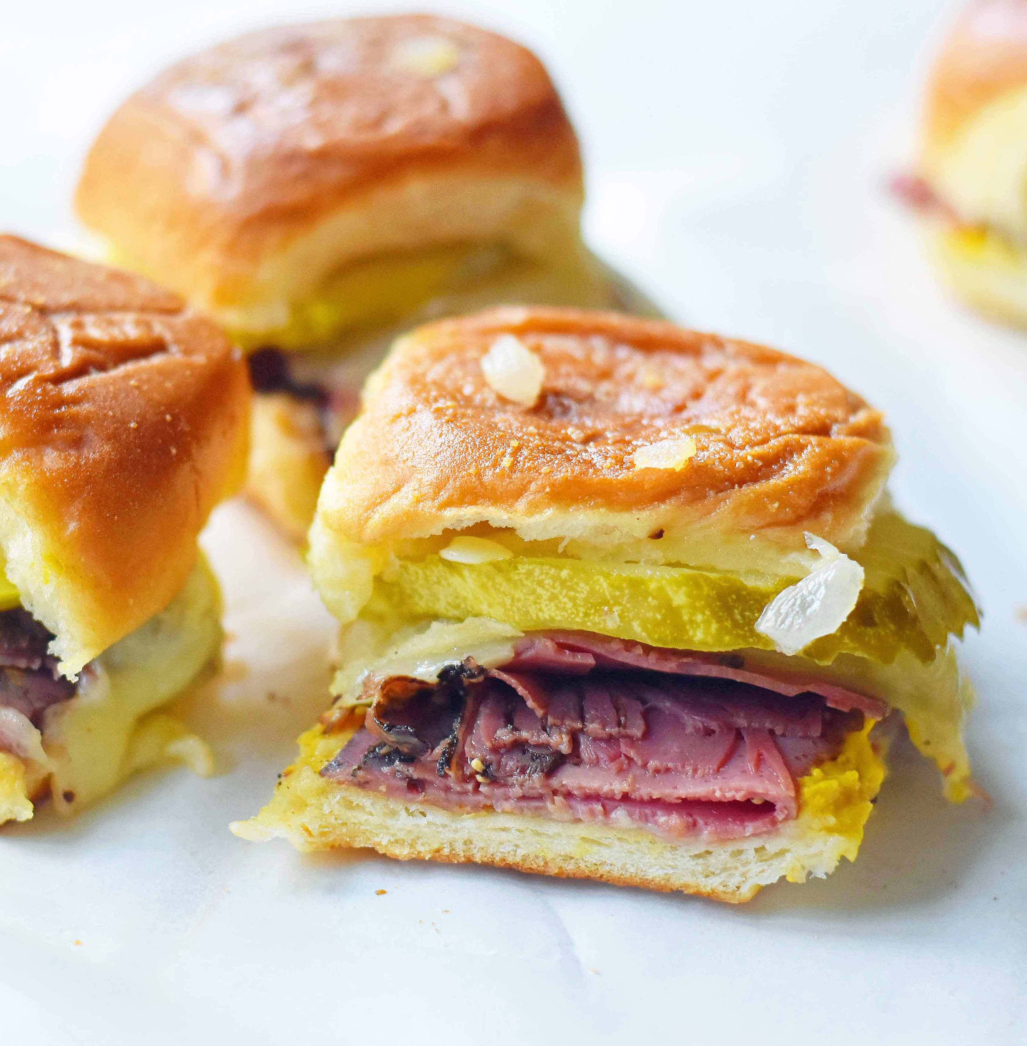 Hot Pastrami and Swiss Tailgate Sliders. Pastrami, creamy swiss, tangy mustard all on a hawaiian roll basted with garlic butter and baked until warm and toasty. A flavorful hot pastrami sandwich that is so easy! Perfect for entertaining, watching a football game, or a dinner at home. www.modernhoney.com
