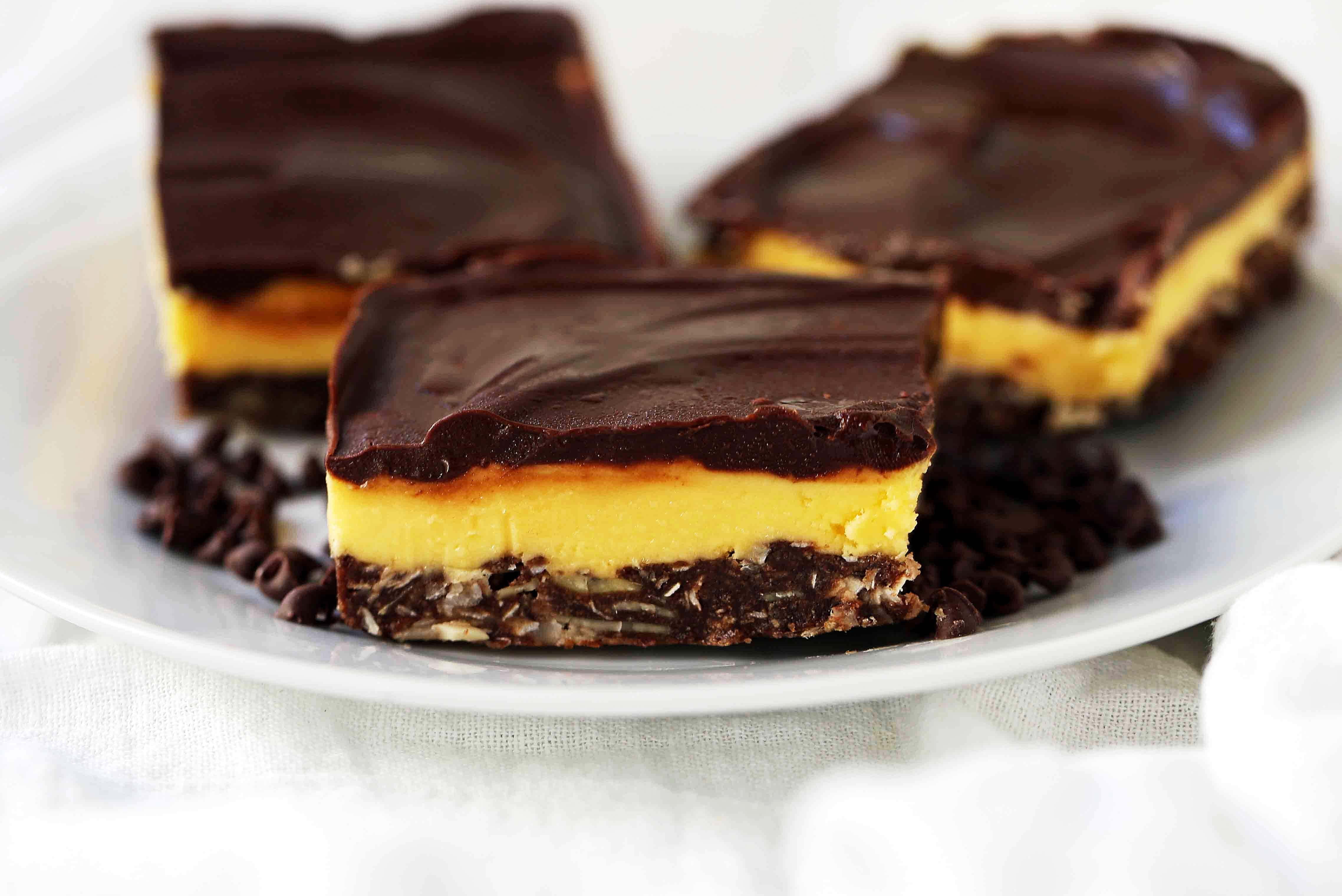 Nanaimo Bars are a famous Canadian dessert bar. A triple layer bar with a crust made with graham crackers, coconut, chocolate, and almonds, and a filling made with custard and cream, and covered in a chocolate ganache. www.modernhoney.com #nanaimobars #nanaimo #triplelayerbars #dessertbar
