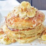 Toasted Coconut Macadamia Pancakes with Coconut Syrup are the most perfect tropical pancakes. Light and fluffy toasted coconut pancakes topped with homemade coconut syrup and macadamia nuts. www.modernhoney.com