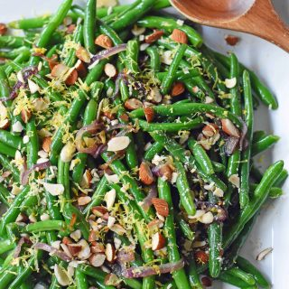 Green Beans with Almonds and Caramelized Onions. Light and fresh green beans sauteed with caramelized onions, fresh lemon zest, and crunchy almonds. Perfect side dish for your holiday table. www.modernhoney.com