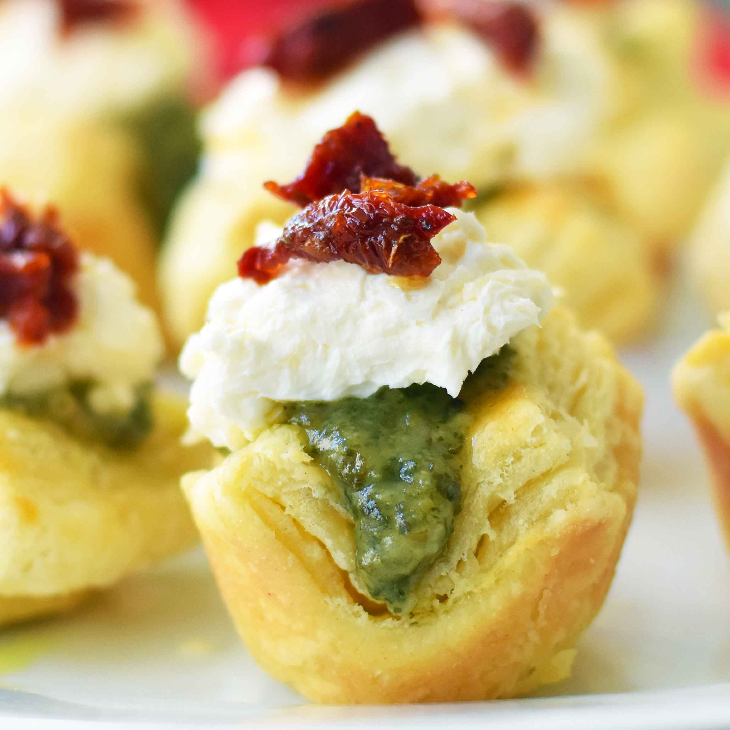 Pesto Parmesan Sundried Tomato Tartlets are made with flaky puff pastry baked until golden brown and filled with Buitoni freshly made pesto sauce, a parmesan goat cheese cream cheese layer, and topped with sweet sundried tomatoes. A beautiful and festive holiday appetizer. www.modernhoney.com @buitoniusa #sponsored