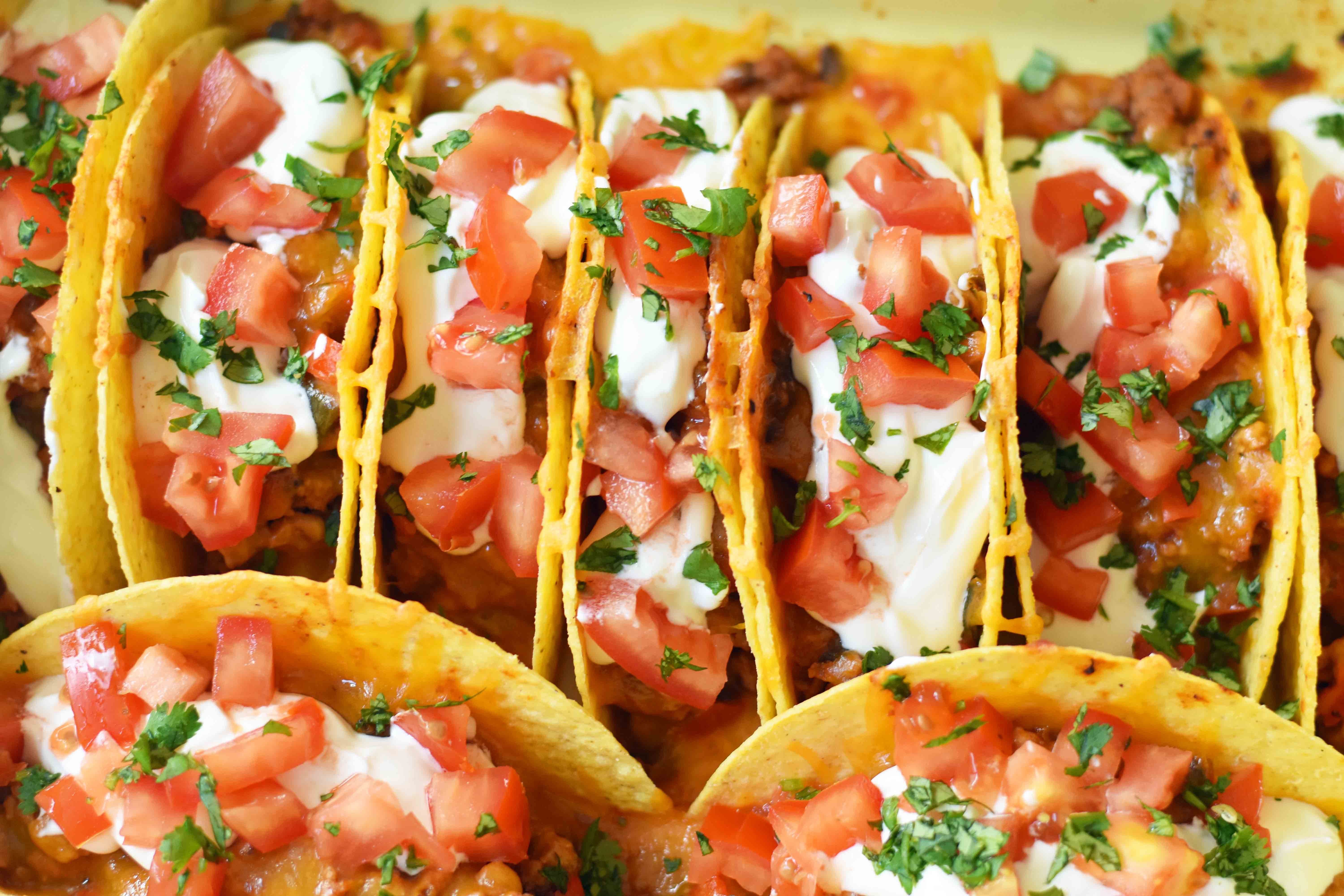 Easy Oven Baked Beef Tacos. Perfectly seasoned ground beef tacos and Mexican cheese baked in taco shells until melted. Topped with sour cream, guacamole, salsa, diced tomatoes, and hot sauce. These are party tacos and a family favorite dinner. www.modernhoney.com