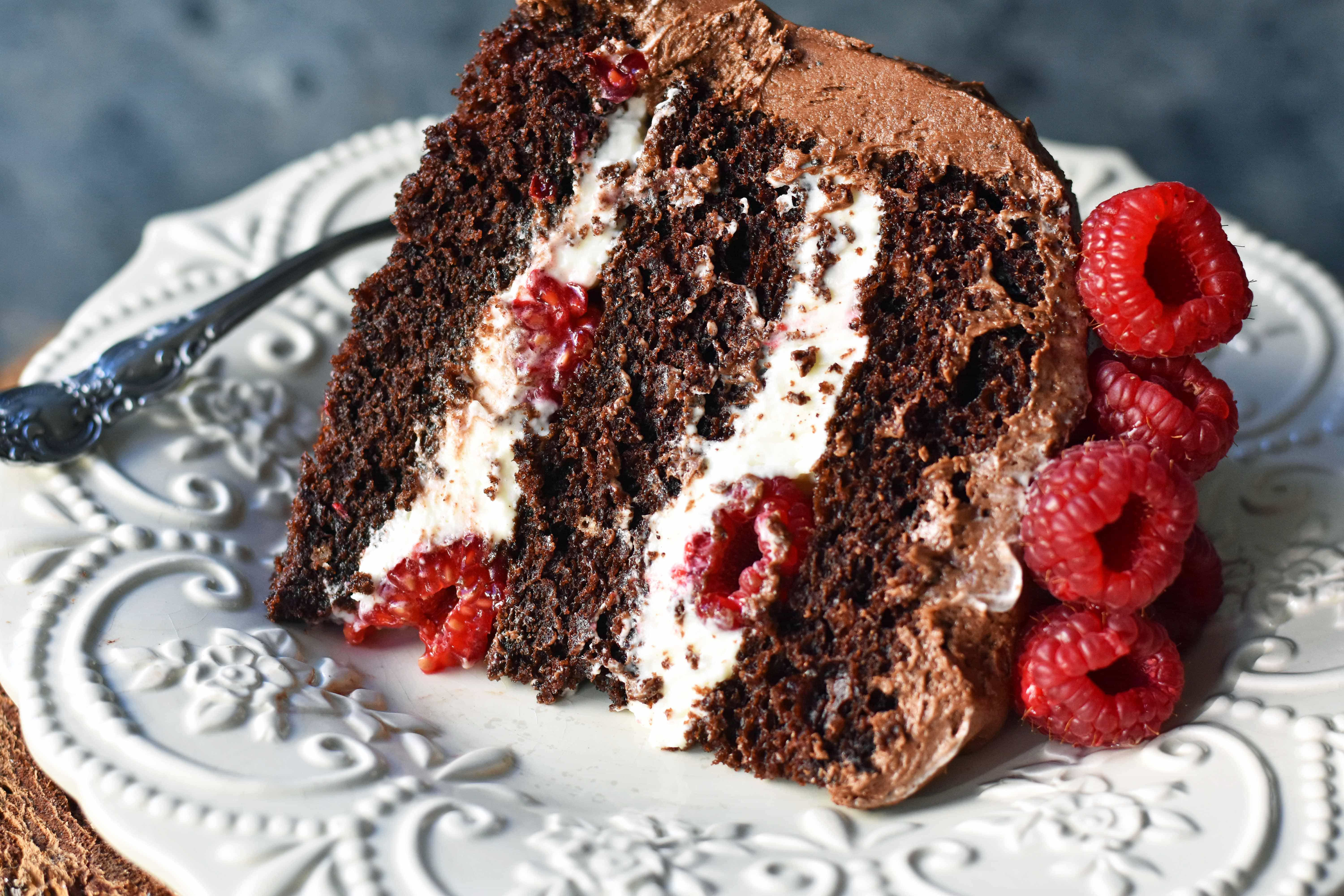 Rich chocolate cake layered with whipped cream cheese raspberry filling, topped with creamy chocolate frosting and fresh raspberries. Homemade BEST EVER Chocolate Cake with sweet whipped cream cheese raspberry filling topped with chocolate buttercream and raspberries. www.modernhoney.com