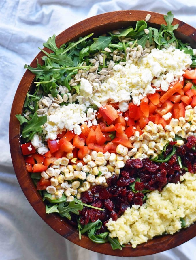 Chopped Salad with fresh arugula, dried cranberries, crunchy red peppers, feta cheese, sweet corn, and couscous tossed with a creamy basil dressing. A Wildflower copycat recipe. www.modernhoney.com