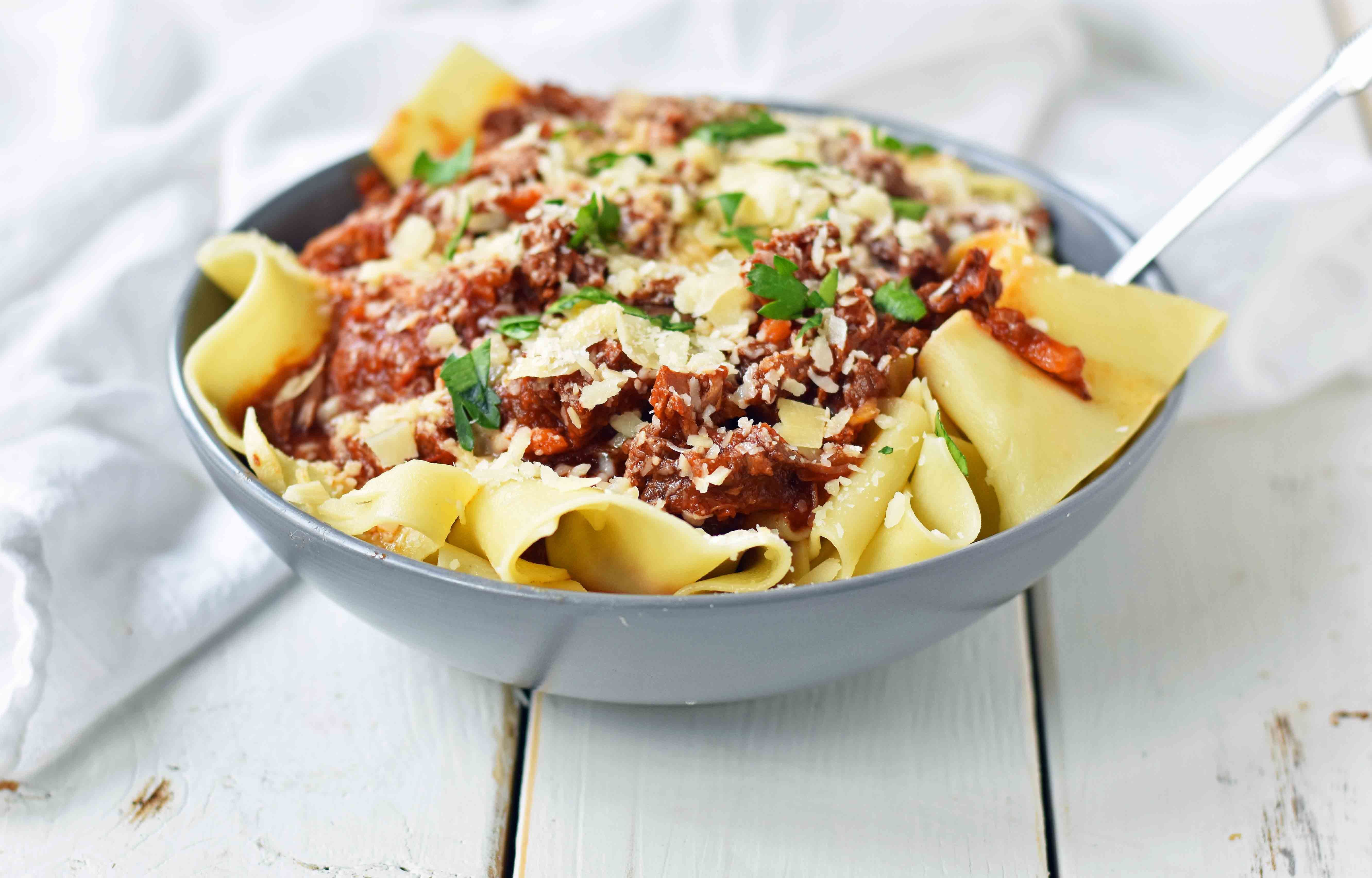 Slow Cooker Instant Pot Beef Ragu. This braised shredded beef ragu with pappardellepasta can be made in a slow cooker or instant pot pressure cooker. It makes the most tender, flavorful beef in a rich, velvety sauce. It is the ultimate comfort meal in a bowl! This Beef Ragu can be put on top of spiralized vegetables, mashed potatoes, or polenta for a gluten-free dinner. www.modernhoney.com
