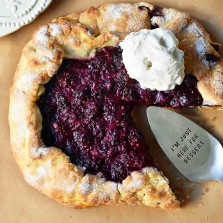 Blackberry Galette Crostata. An easy rustic summer dessert made with homemade buttery flaky pie crust with a sweet blackberry filling topped with vanilla bean ice cream. A much easier blackberry pie! www.modernhoney.com #galette #crostata #blackberrycrostata #blackberrygalette #summerdessert #berrydessert