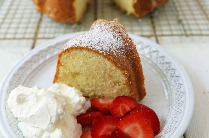 The BEST Cream Cheese Pound Cake with fresh strawberries and whipped cream. How to make the perfect pound cake in a bundt pan. Buttery cream cheese pound cake goes with everything! This is such a popular cake that is wonderful on its own or in a trifle or berry compote. www.modernhoney.com #poundcake #bundtcake #cake #creamcheesecake