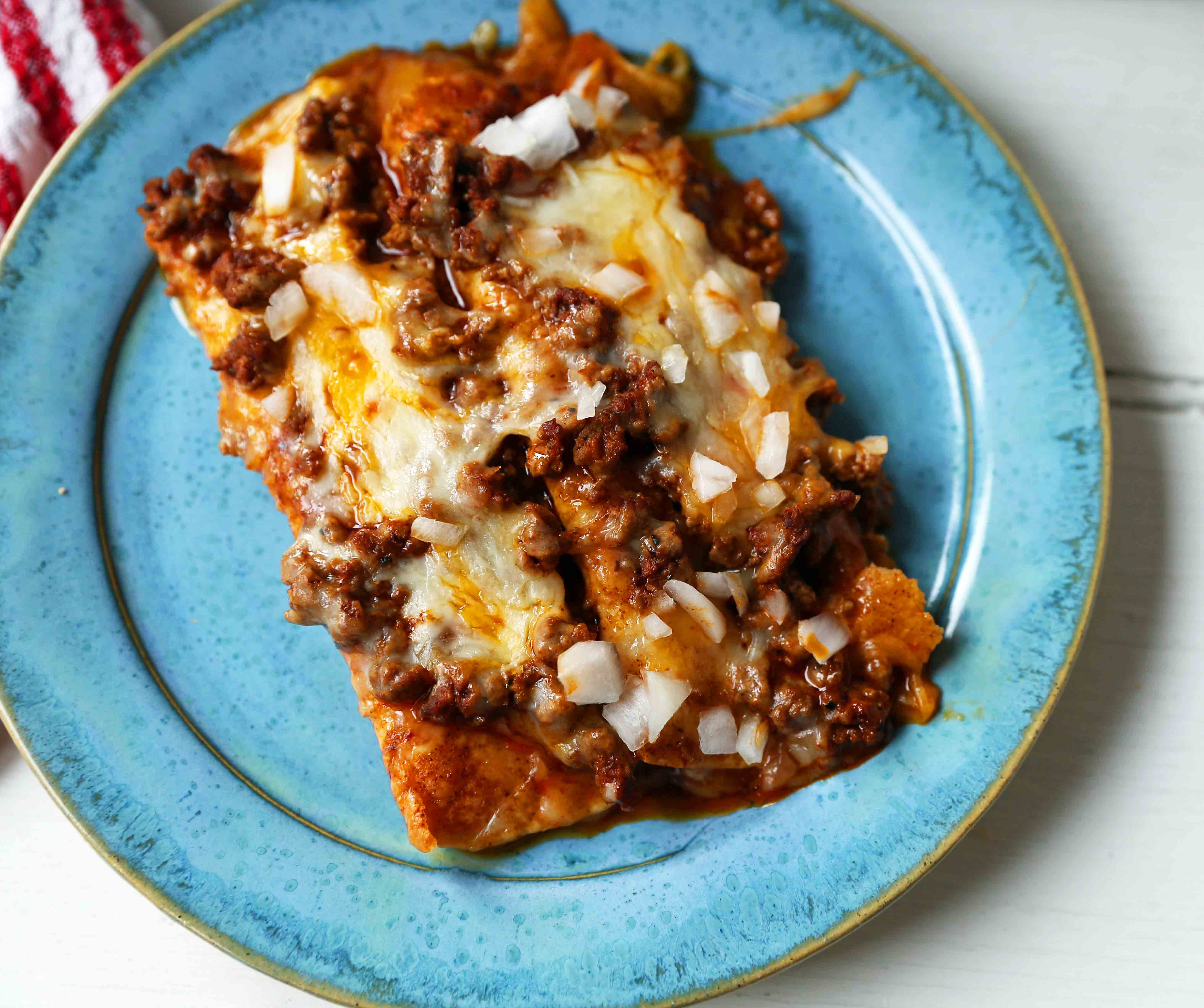 Chile con Carne Enchiladas. Authenic Tex-Mex Beef Enchiladas Recipe. Cheese Enchiladas topped with homemade chile con carne. The best chile con carne enchiladas recipe! #chiliconcarne #texmex #texmexenchiladas #enchiladas #mexicanfood