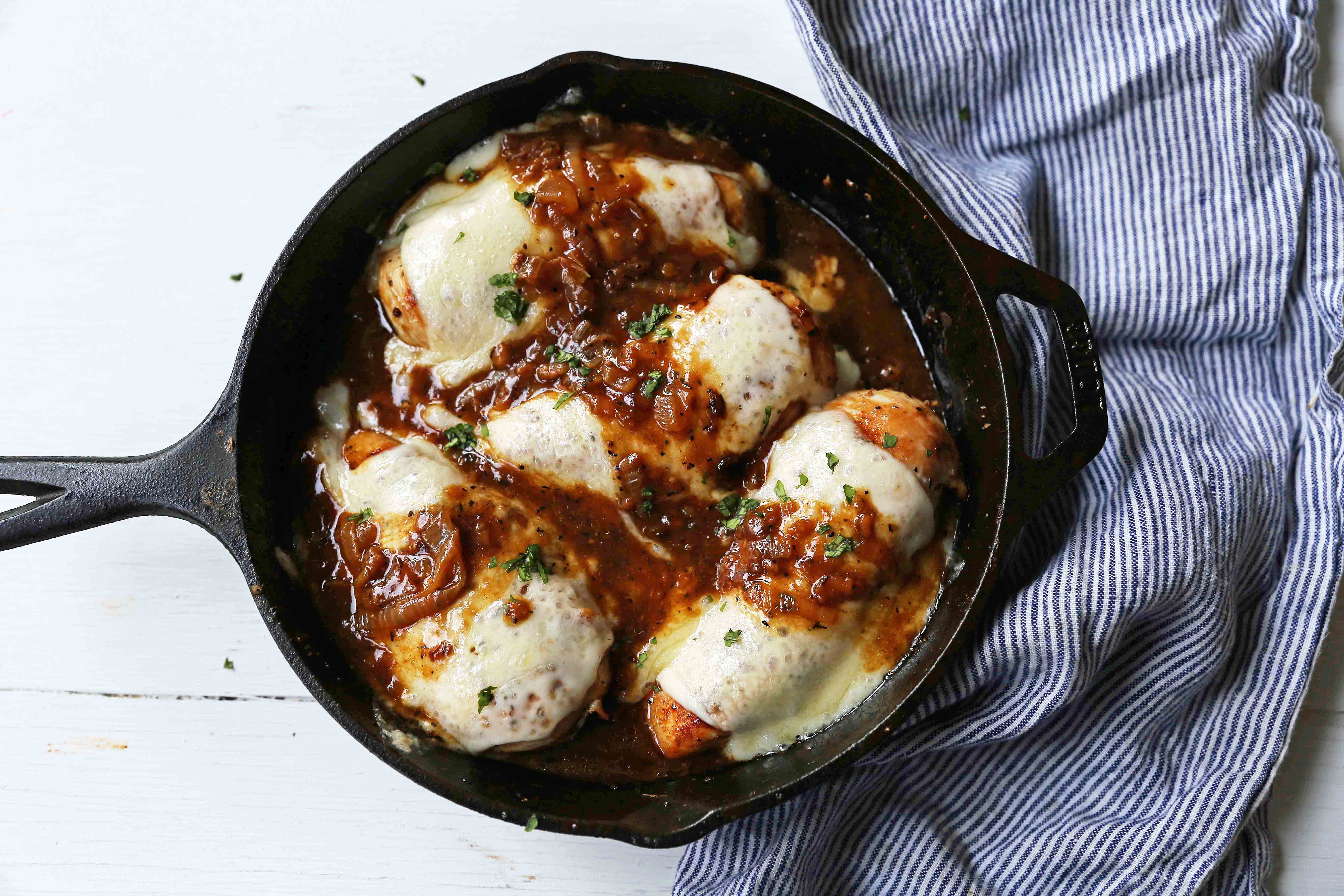 French Onion Chicken Skillet Chicken with Buttery Caramelized Onion Gravy and Melted Cheeses. A simple, flavorful, 30-minute meal! www.modernhoney.com #30minutemeal #dinnerrecipe #frenchonionchicken #cheesychicken #chickendinner