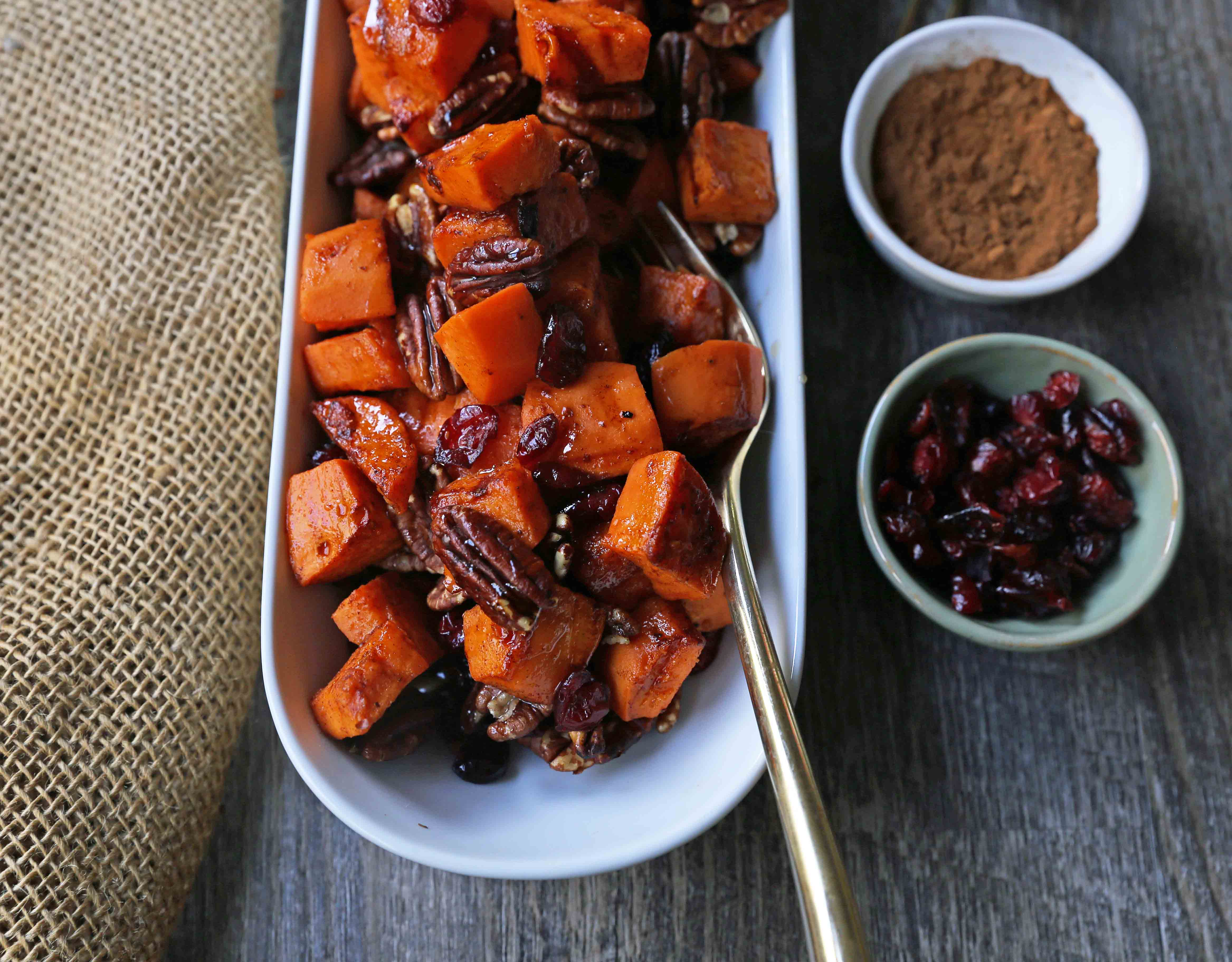 Roasted Sweet Potatoes with Pecans and Cranberries An easy, healthy side dish made with cinnamon roasted sweet potatoes, toasted pecans, and sweet and tart dried cranberries. www.modernhoney.com #sidedish #sweetpotatoes #sweetpotatoespecan #roastedsweetpotatoes