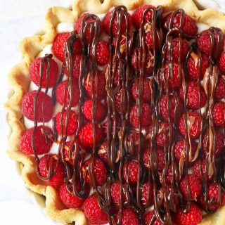 Raspberry Almond Cream Cheese Pie. A simple cream cheese almond pie with fresh raspberries and chocolate drizzle. An award-winning easy pie recipe! www.modernhoney.com #creamcheesepie #raspberrypie #pie #pierecipe #driscolls