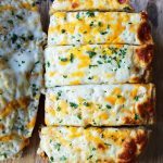 Quick and Easy Garlic Cheese Bread. Warm bread toasted and slathered with garlic butter and melted ooey gooey cheese. Garlic Cheese Bread is the perfect side dish or appetizer. www.modernhoney.com #appetizer #sidedish #garlicbread #garliccheesebread #cheesebread