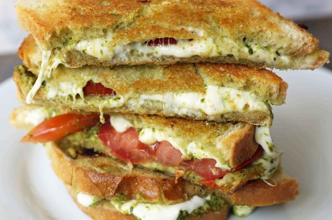 Pesto Panini with Fresh Mozzarella and Tomato. A toasted buttery panini with basil pesto, melted fresh mozzarella cheese, and juicy tomatoes. www.modernhoney.com #panini #sandwich #pesto #grilledsandwich