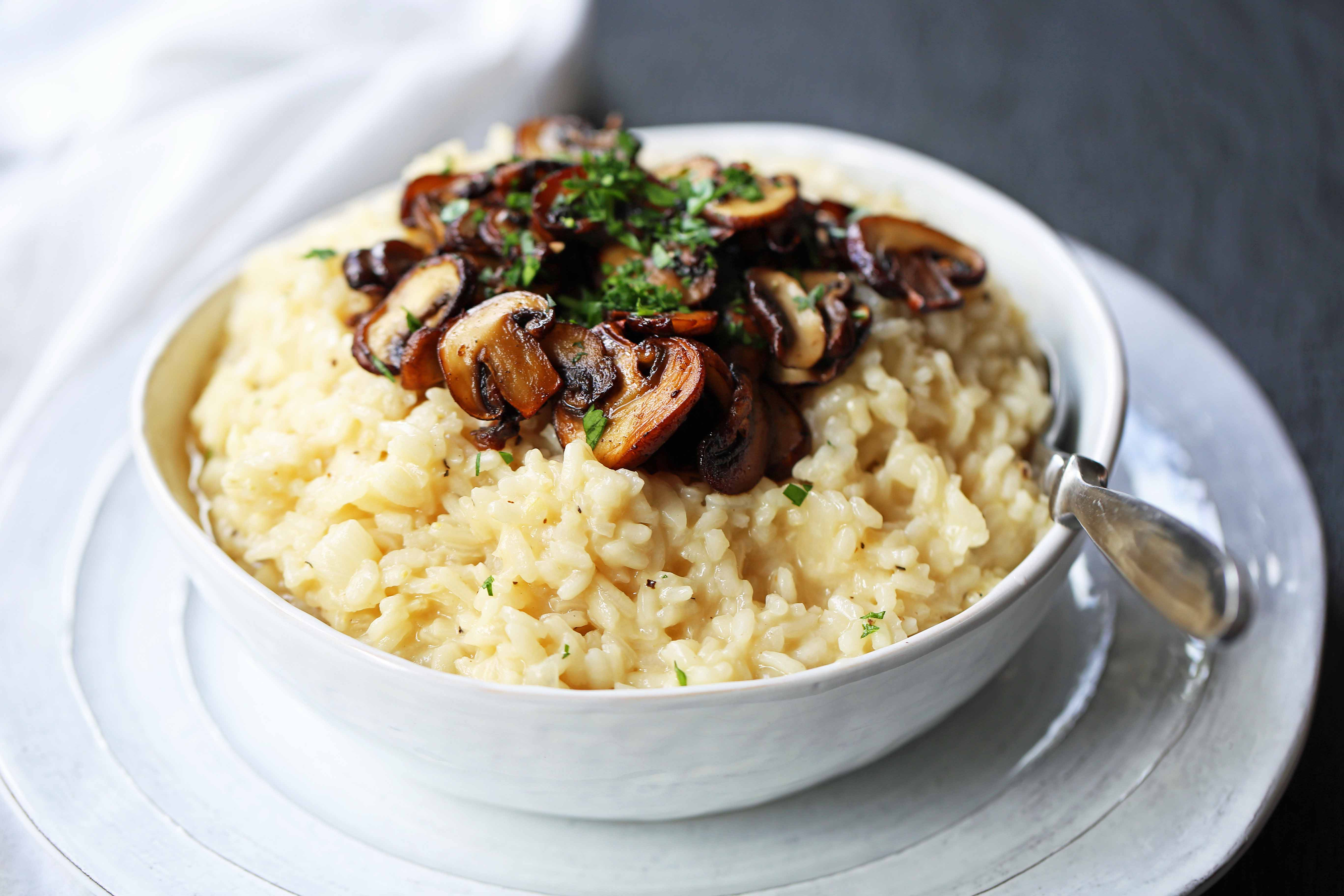 Creamy Mushroom Risotto. Rich, creamy rice slowly simmered with chicken broth, butter, parmesan cheese, and topped with butter sauteed mushrooms. www.modernhoney.com #risotto #homemaderisotto #mushroomrisotto