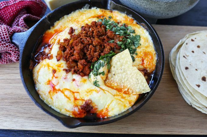 Queso Fundido with Chorizo. A skillet of melted Mexican cheeses seasoned with peppers, onions, and spicy Mexican chorizo sausage and served with hot tortillas or chips. The perfect Mexican appetizer! www.modernhoney.com #appetizer #appetizers #mexican #mexicanfood #queso #quesofundido