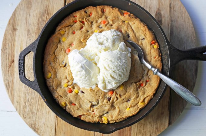 Peanut Butter Skillet Cookie. Homemade peanut butter cookie dough with Reeses Pieces baked until ooey gooey and topped with vanilla ice cream and hot fudge. www.modernhoney.com #peanutbutter #peanutbuttercookies #peanutbutterpizookie #pizookie