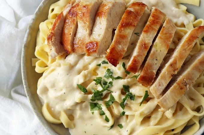 Chicken Fettucine Alfredo. Creamy parmesan cream sauce tossed with fettuccine pasta and topped with sauteed chicken. How to make the best chicken fettuccine alfredo. www.modernhoney.com #fettuccinealfredo #chickenfettuccinealfredo #pasta