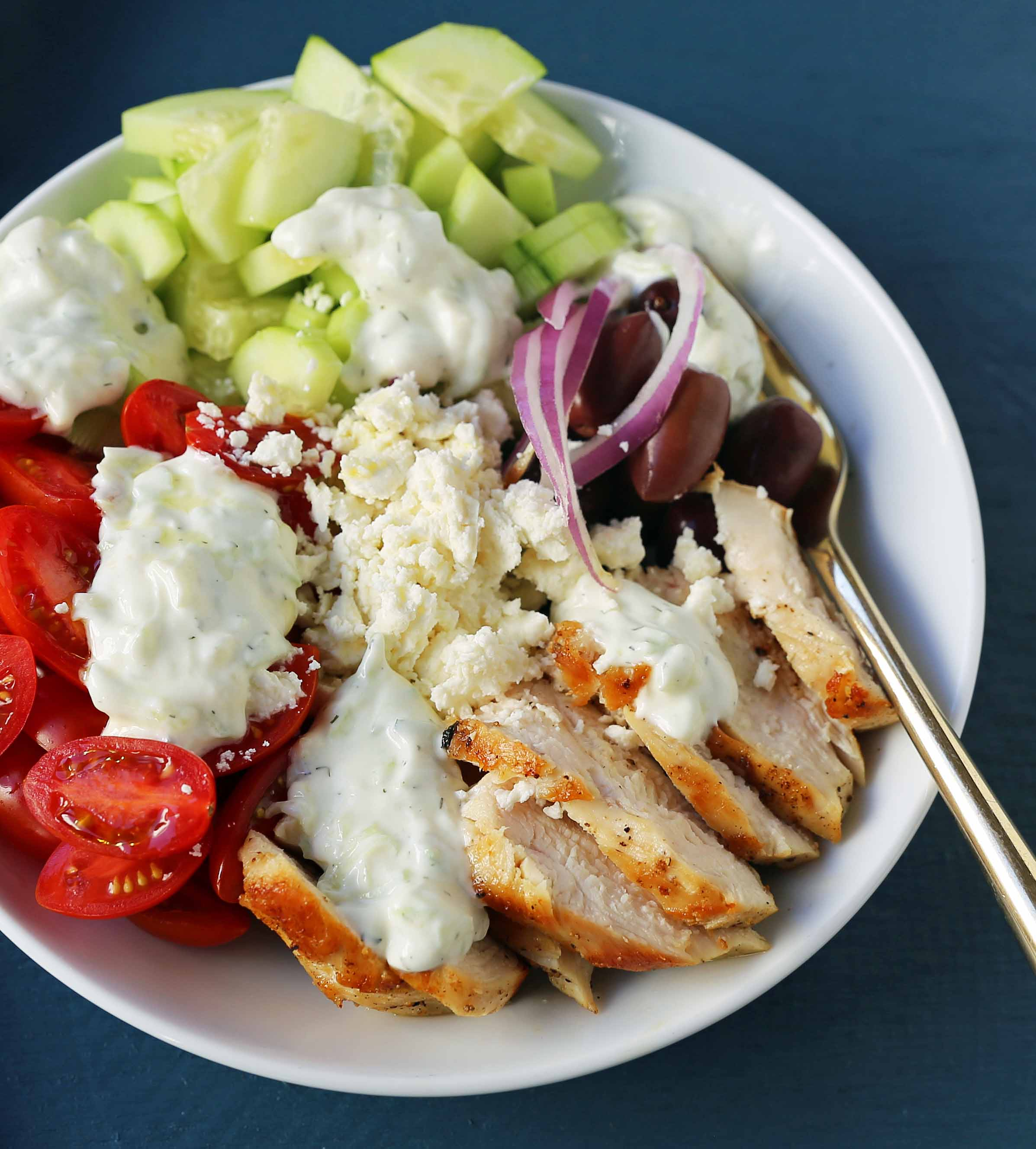 Greek Chicken Bowls. Grilled Greek Lemon Chicken, cucumber, tomatoes, red onion, kalamata olives, feta cheese, and homemade tzatziki sauce all in one bowl. A high-protein and low carb meal! www.modernhoney.com #greekchickenbowls #greekchickenbowl #greekfood #glutenfree