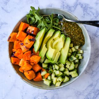 Buddha Bowl with Pistachio Pesto A healthy vegan bowl made with roasted sweet potatoes, onions, fresh avocado, cucumbers, arugula, quinoa, and homemade pistachio pesto. www.modernhoney.com #buddhabowl #vegan #vegetarian #flowerchild