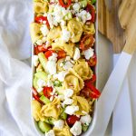 Greek Tortellini Pasta Salad. Cheese Tortellini Pasta tossed with fresh tomatoes, cucumbers, red onion, feta cheese, in a homemade Greek dressing. www.modernhoney.com #sidedish #pastasalad #salad #potluck